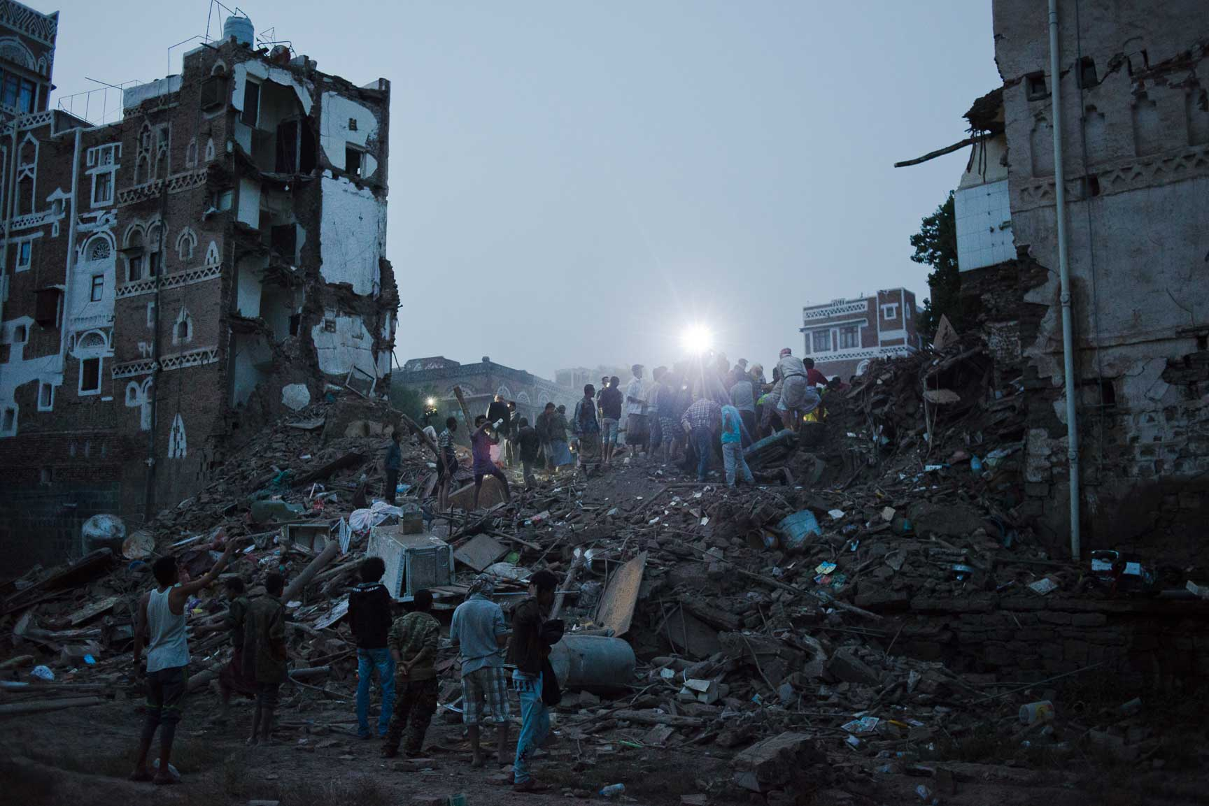 Yemeni men from al Qasimi neighborhood dig through the remains of four homes destroyed in an airstrike Friday, June 12, 2015 in Sana'a, Yemen. The Old City of Sana'a is a UNESCO World Heritage Site, is a densely populated civilian area. The Saudi-led coalition denied hitting the Old City.