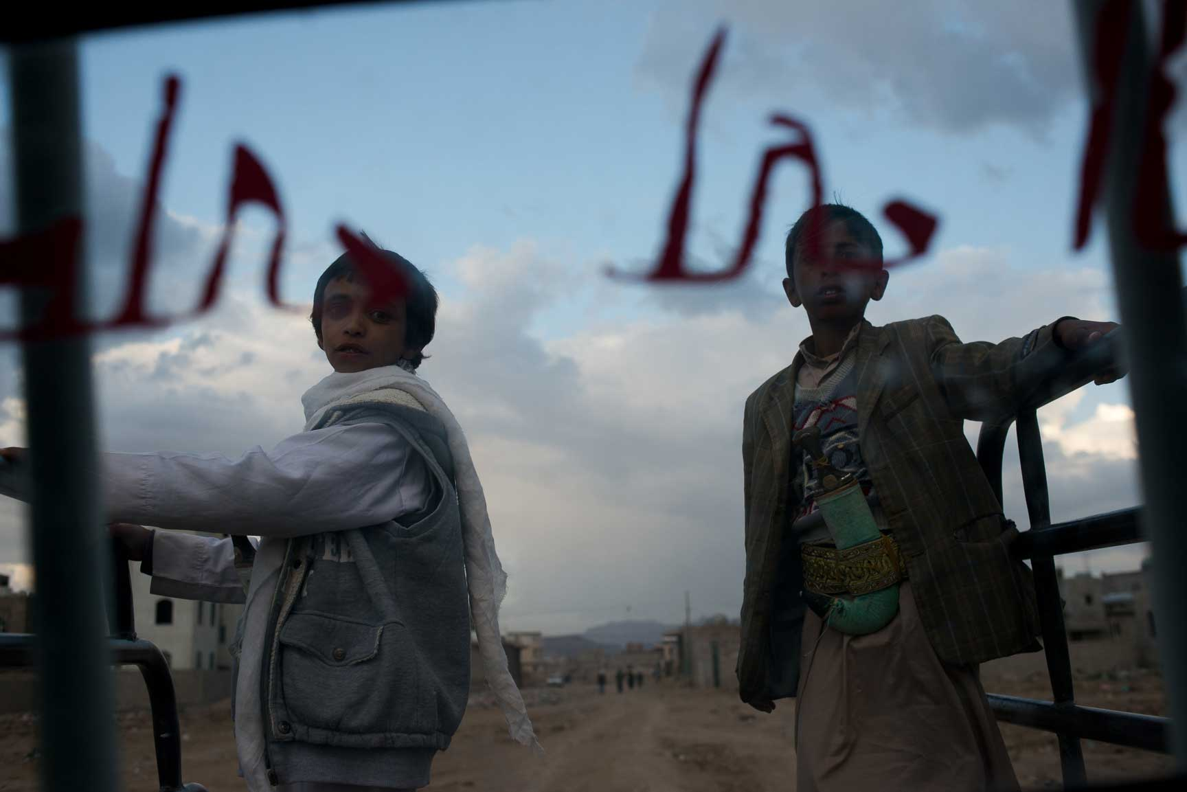 Yemeni boys hitch a ride on the back of a pickup truck on the outskirts of the capital on May 29, 2015. The lack of fuel has severely limited movement for Yemeni's, especially effecting those who need to get to hospitals quickly after airstrikes.