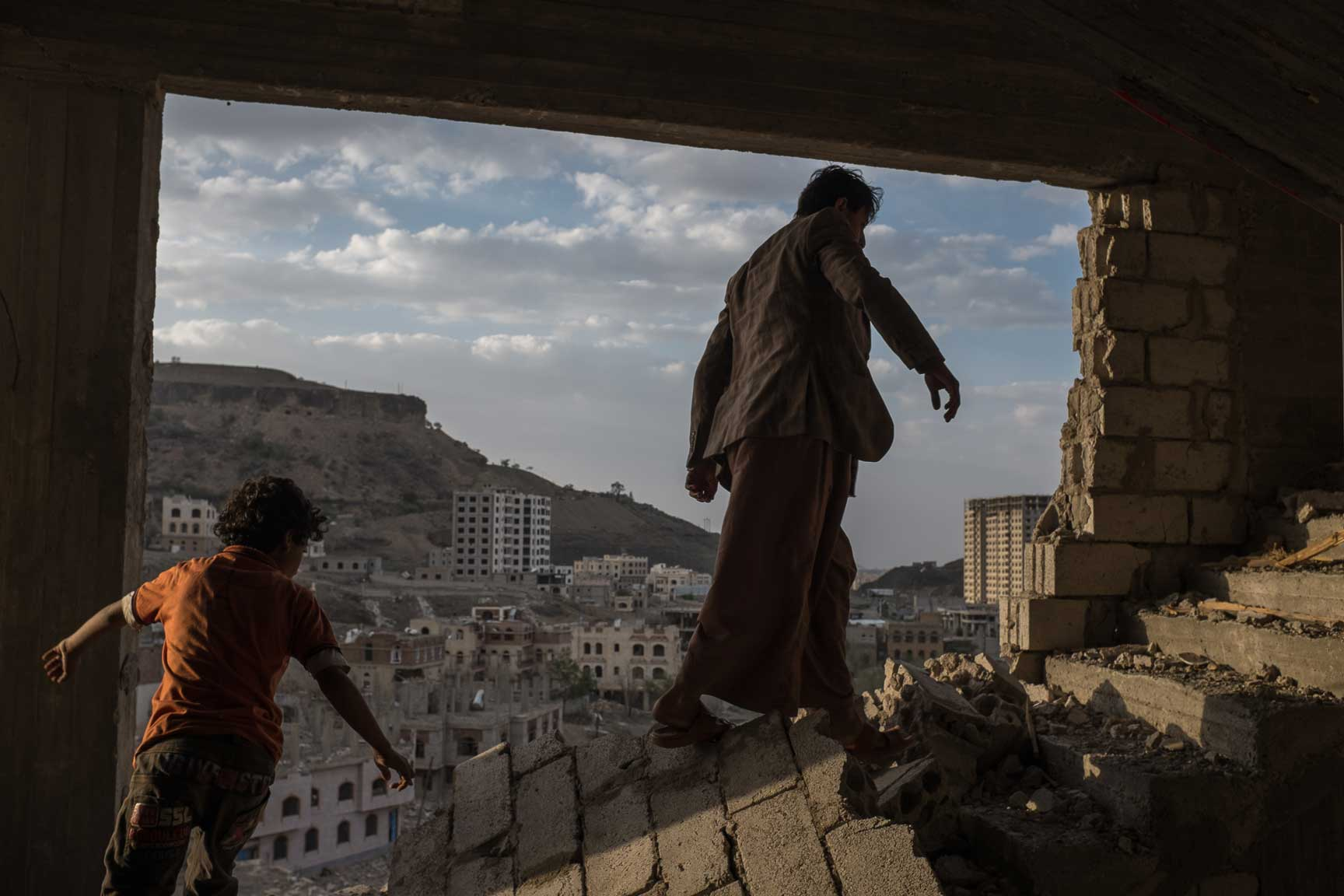Yemeni brothers climb the remains of an apartment building in Faj Attan, a district in Yemen heavily targeted by airstrike, Monday Auugst 17, 2015 in Sana'a, Yemen.