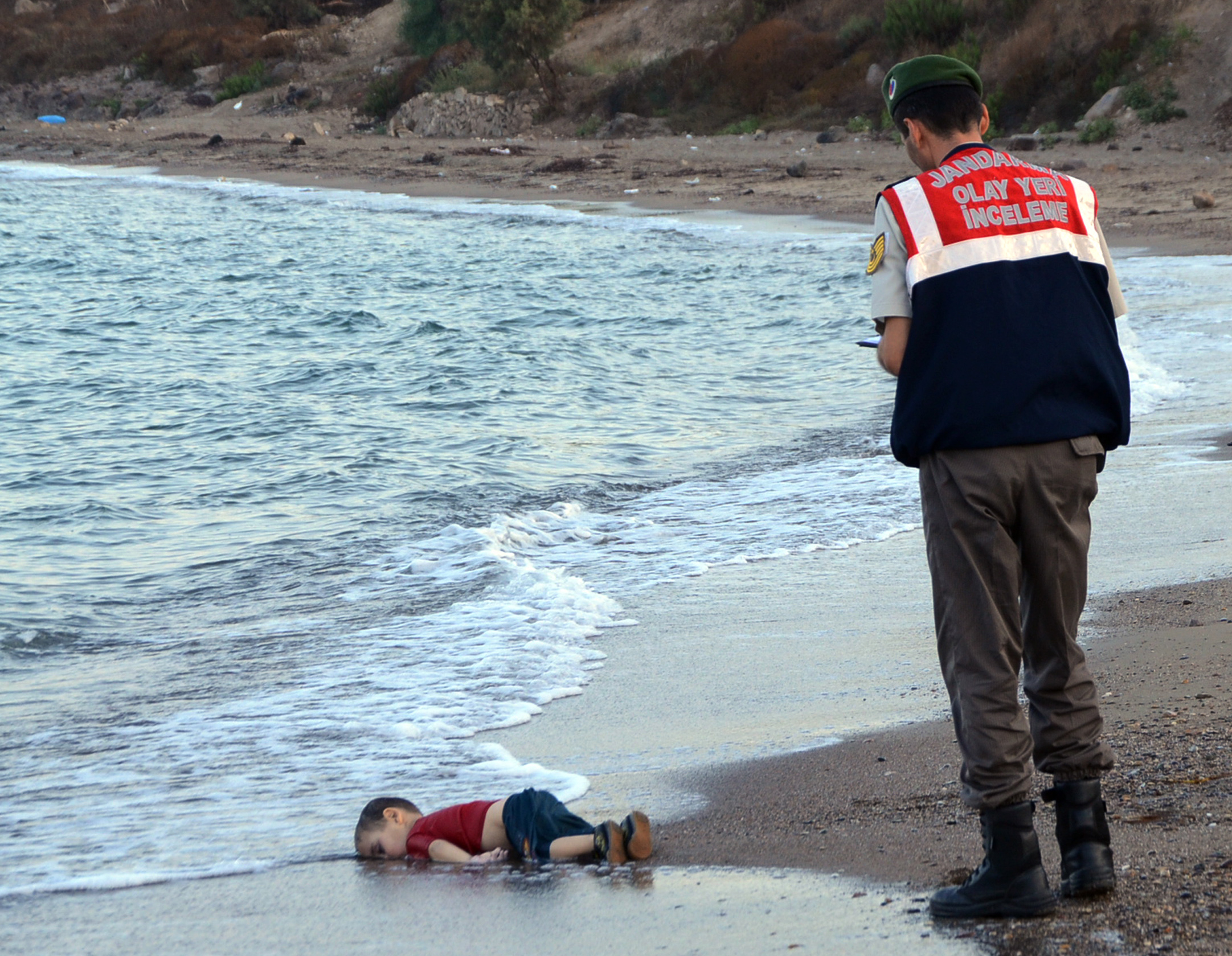 A paramilitary police officer investigates the scene before carrying the lifeless body of Alan Kurdi, 3, after a number of migrants died and others were reported missing when boats carrying them to the Greek island of Kos capsized near the Turkish resort of Bodrum on Sept. 2, 2015.