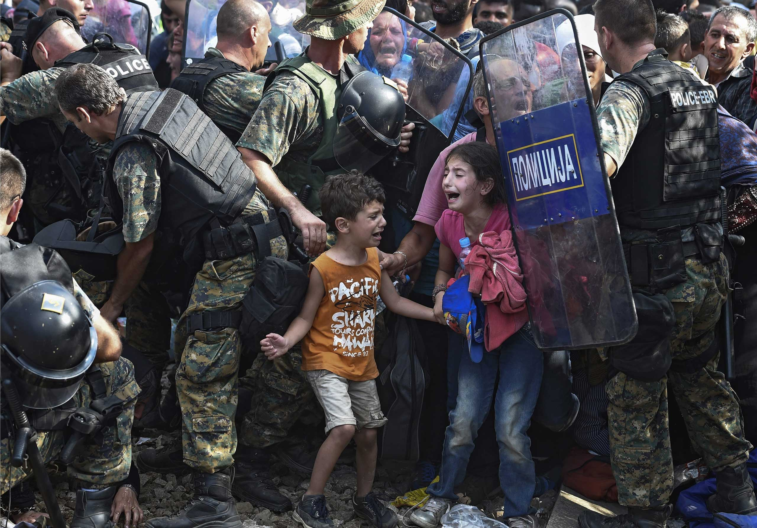 Georgi Licovski:  The Macedonian police were given an order to shut down the illegal passage and not to let anyone through until a solution was found for the transfer of huge number of refugees that were coming from Greece. The police had their orders but the migrants had their agenda. They tried to pass the police cordon by putting the women and children in the front. The men started pushing. The police started letting through some of the women and children, and suddenly there was mass confusion and chaos all around.                                                               That was a day I will never forget. It was the first time I saw my colleagues cry and take pictures, shaken by the terrified children's faces that were trying to find their parents, brothers or sisters in the chaos. I was taking pictures with the intention of showing the world what was happening so that no child should ever live through this again. With time and distance, I can now say that the police weren't being violent, they had orders not to let anyone pass, but the desperation of the refugees was much bigger than the policemen's shields.                                                               This picture is very important for me, maybe one of the most important in my career, because of its many publications in newspapers around the world. [It forced] the political elite [in my country] to approach the migrant problem more seriously.                                                              This photo was taken on the Greek side of the border into Macedonia, near the southern city of Gevgelija on Aug. 21, 2015.
