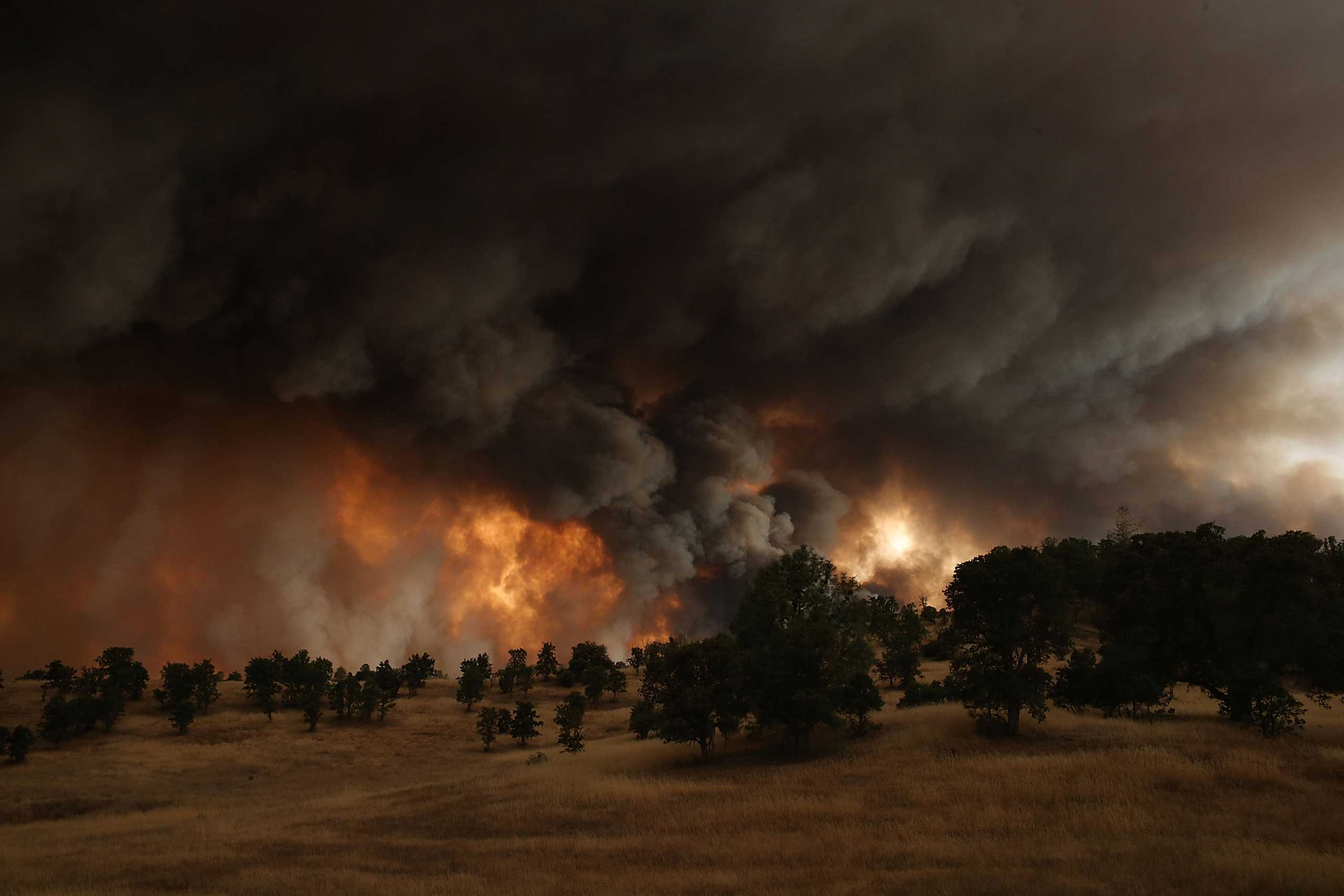 Justin Sullivan:                                 The Rocky Fire had been burning for days when this photo was taken. On this particular day it was raging through tinder dry brush due to four years of severe drought. The stubborn fire exploded to nearly double its size within hours, charring more than 20,000 acres in less than 24 hours.                                                               In my years covering wildfire, I have never seen a fire grow so quickly. It was a surreal scene to be sitting along highway 20 with dozens of firefighters who were essentially waiting for the fire to come to them. The black columns of smoke filled the sky and the light from the setting sun filtered through, casting eerie light onto the landscape. It was mesmerizing to watch the thick smoke as it slowly rose from the hills.                                                               The flames reached highway 20 after 2AM and were met by dozens of fire crews who lit back fires to help contain it and keep it from jumping the road.                                                                This photo was taken near Clearlake, Calif. on Aug. 1, 2015.