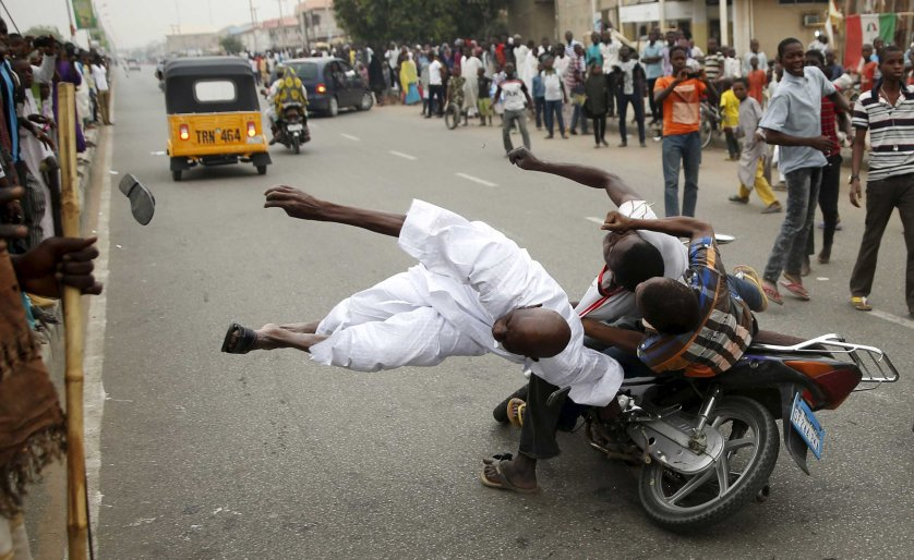 Supporters of the presidential candidate Muhammadu Buhari and his All Progressive Congress hits another supporter with a motorbike during celebrations in Kano March 31, 2015. Nigeria's opposition APC declared an election victory on Tuesday for former military ruler Buhari and said Africa's most populous nation was witnessing history with its first democratic transfer of power.