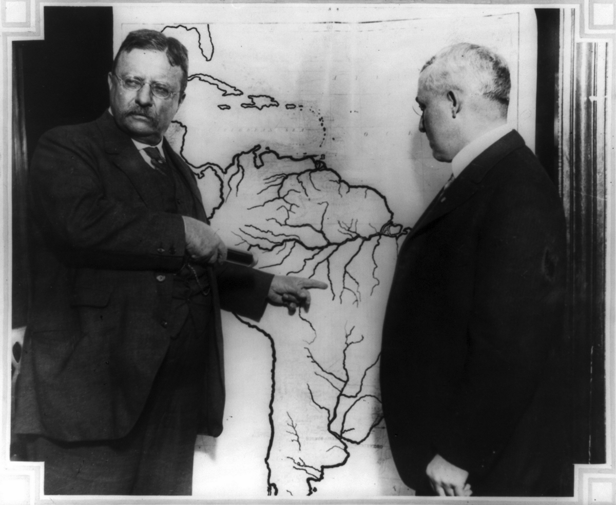 President Roosevelt, in 1915, pointing at a map of South America towards the area explored during the Roosevelt-Rondon Scientific Expedition in Brazil as another man looks on.