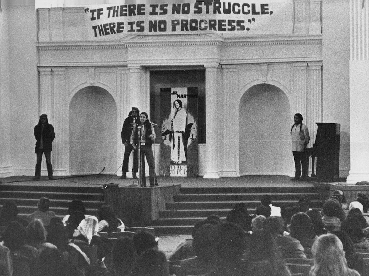 John Trudell, national coordinator of the American Indian Movement, addresses more than 200 Hispanos, other Third World peoples and sympathizers Saturday at a  Tribute to Luis Martinez and Day of Solidarity  on March 21, 1976, in Denver
