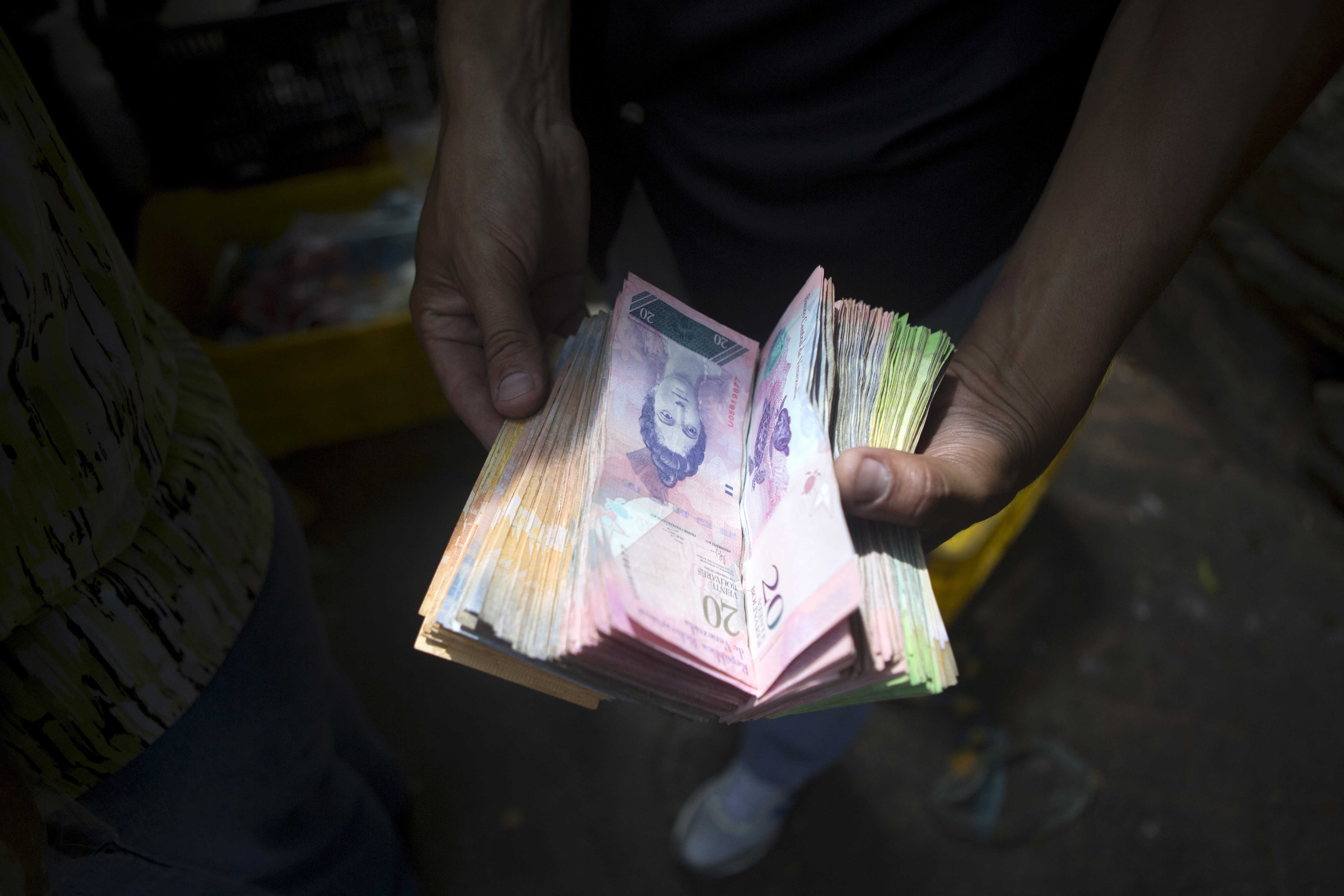 A man displays bolivar notes that he carries to pay for goods at a street market in Caracas on Oct. 1, 2015.