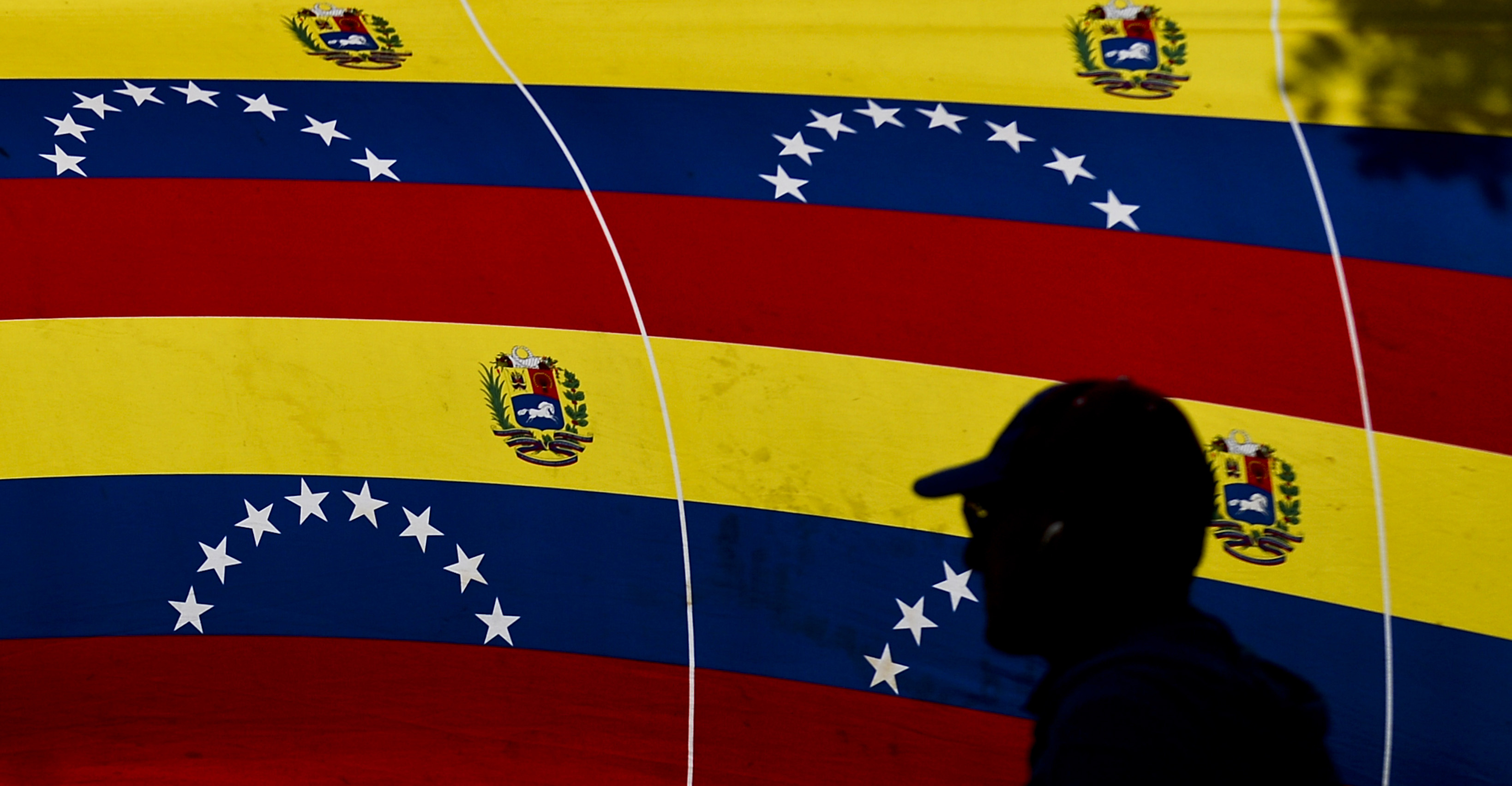 A man passes by national flags at a polling station during Venezuela's legislative election in Caracas on Dec. 6, 2015.