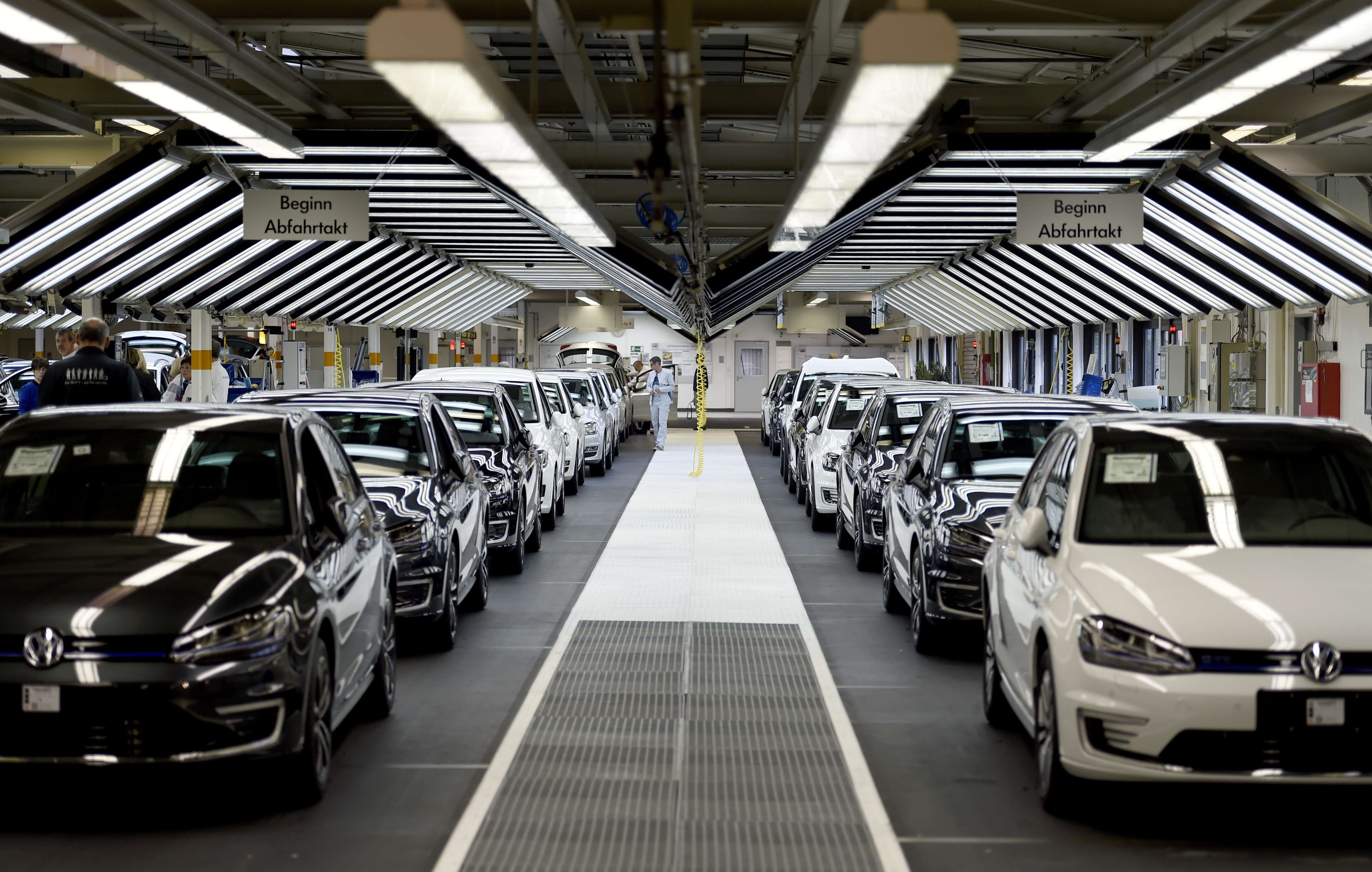 Employees of German car maker Volkswagen check cars at a assembly line of the VW plant in Wolfsburg, Germany, Oct. 21, 2015.