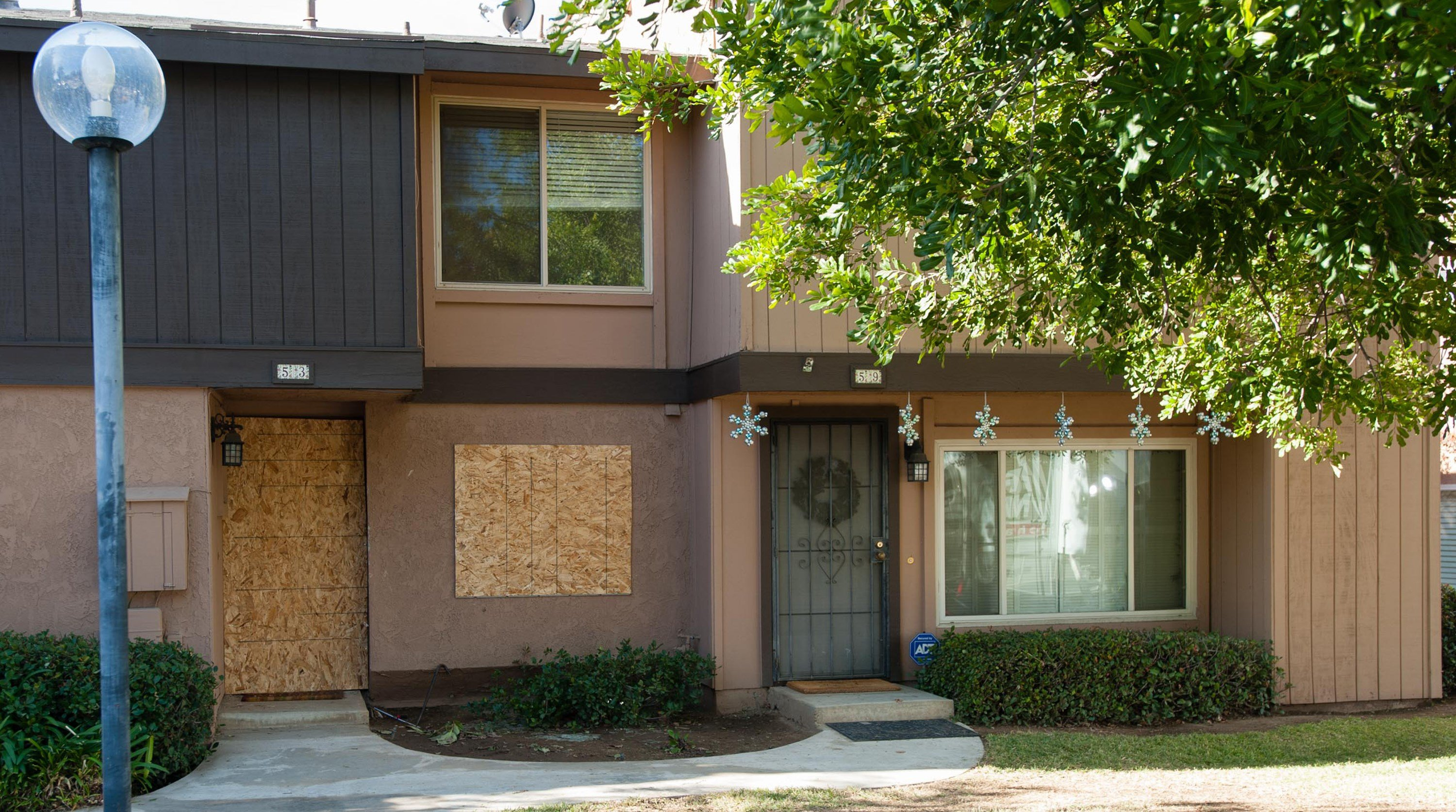 The rented Center Street townhouse of Syed Rizwan Farook and his wife, Tashfeen Malik, is boarded up as holiday decorations and a wreath adorn a neighboring residence on December 5, 2015, in Redlands, CA.