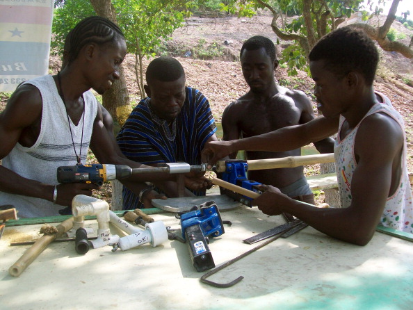 The chief executive officer of the Ghana Bamboo Project, Ibrahim Djan Nyampong (L), and workers assemble on December 10, 2010 bamboo bicycle frames in Sowutuom. The sight of tall, green bamboo stalks swaying above the dusty lands of his west African country led Ibrahim Djan Nyampong to an unusual conclusion: bicycles. Under the shade at a workshop in Ghana, young artisans are making them -- from mountain racers to cargo bamboo bikes -- to suit needs of customers, now as far afield as the United States and Europe.   AFP PHOTO / DAVID ADADEVOH (Photo credit should read David Adadevoh/AFP/Getty Images)