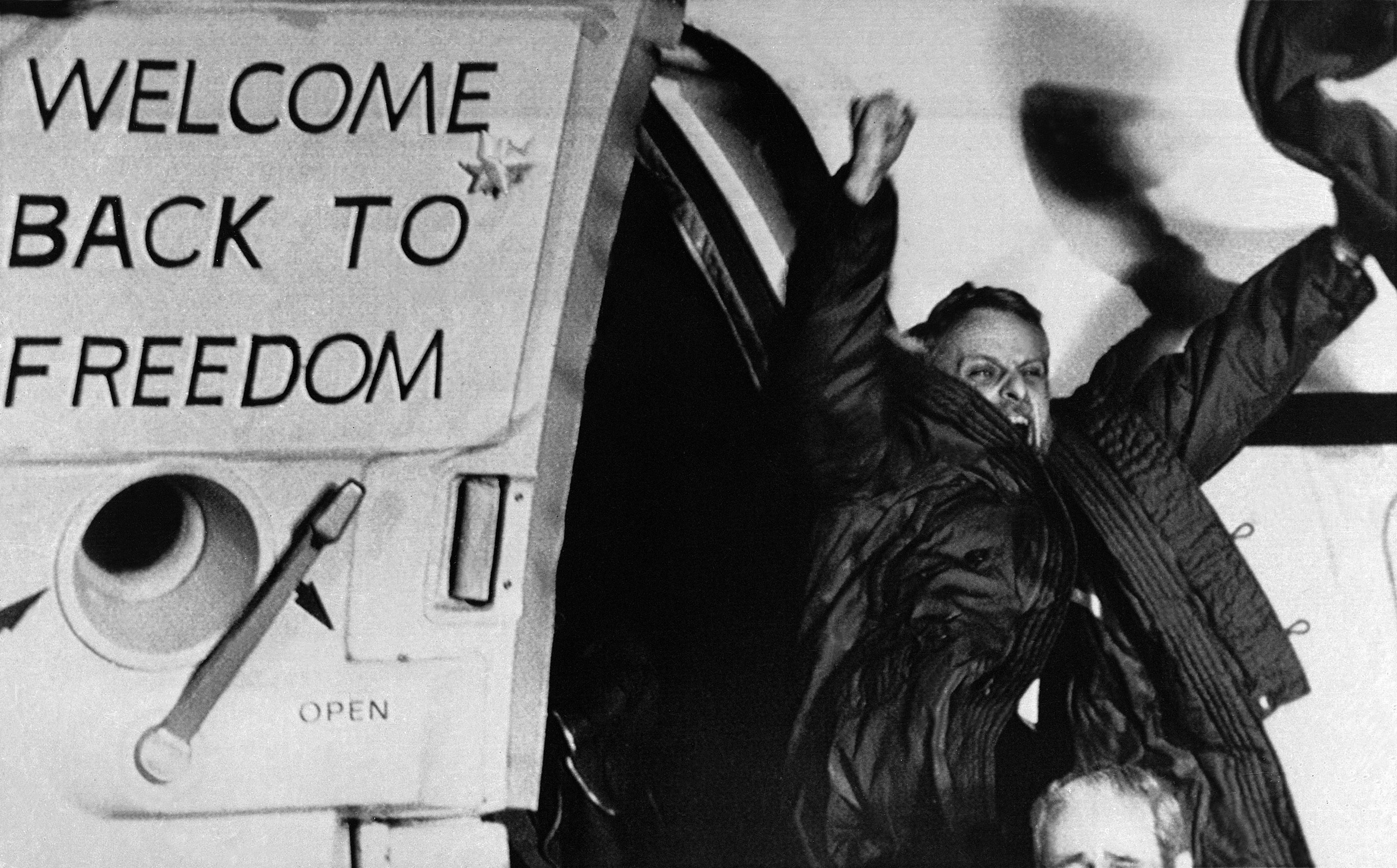 Freed U.S. hostage David Roeder shouts and waves as he arrives at Rhein-Main U.S. Air Force base in Frankfurt, Germany. Roeder was among 52 Americans held hostage in Iran for 444 days after their capture at the U.S. Embassy in Tehran. Jan. 21, 1981.