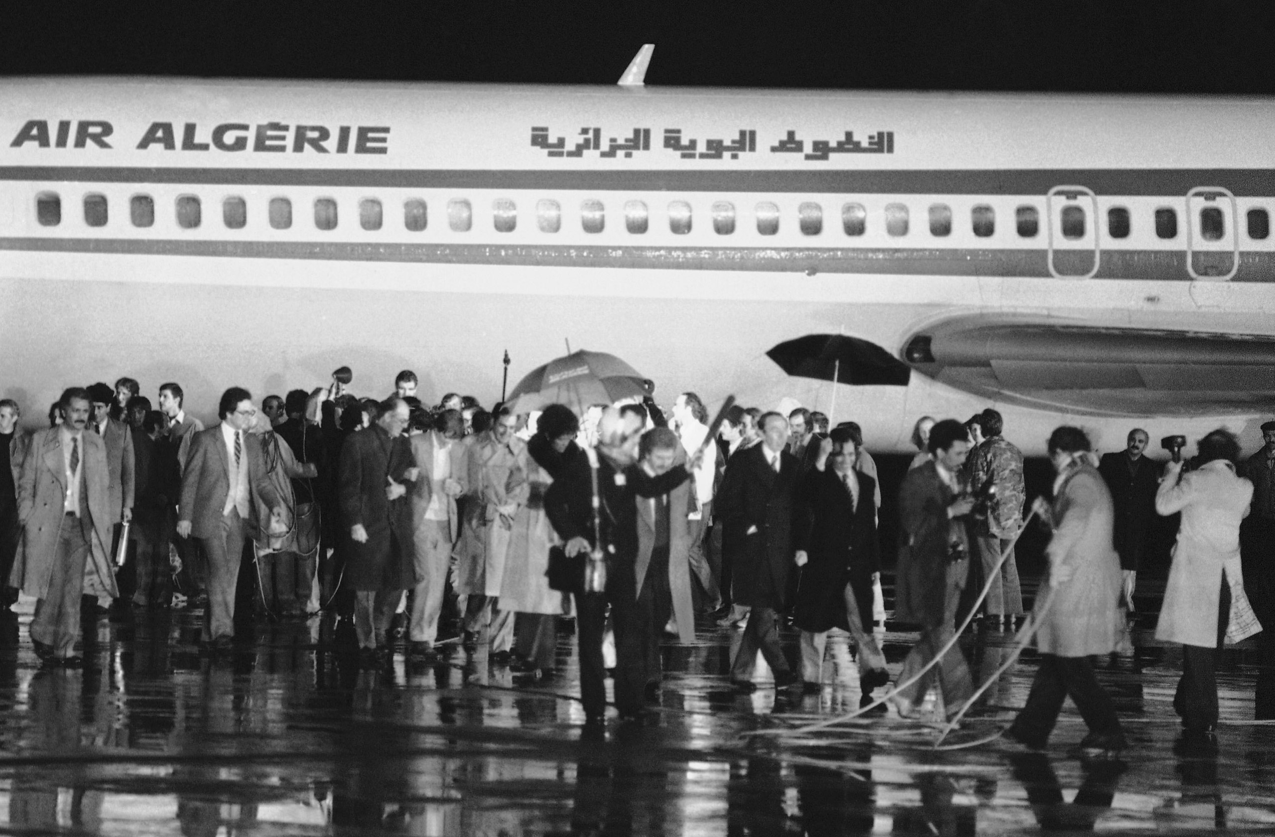 Outgoing US Deputy Secretary of State, Warren Christopher (right) strolls away under an umbrella, as the American hostages freed from Iran, and Algerian officials, gather around the Algerian aircraft that flew the hostages to freedom at Algiers airport, on Jan. 21, 1981.