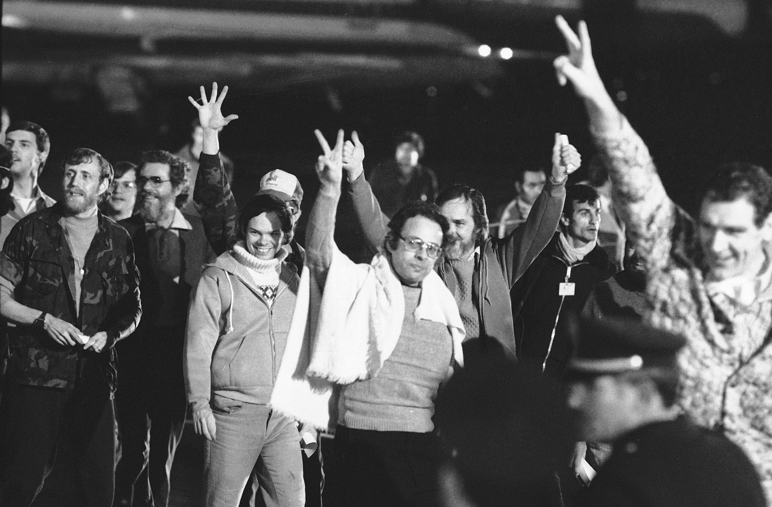 A group of American hostages give the victory sign as they emerge from an Algerian aircraft in Algiers after their flight from Teheran where they had been held captive for 444 days in Iran, Jan. 21, 1981.