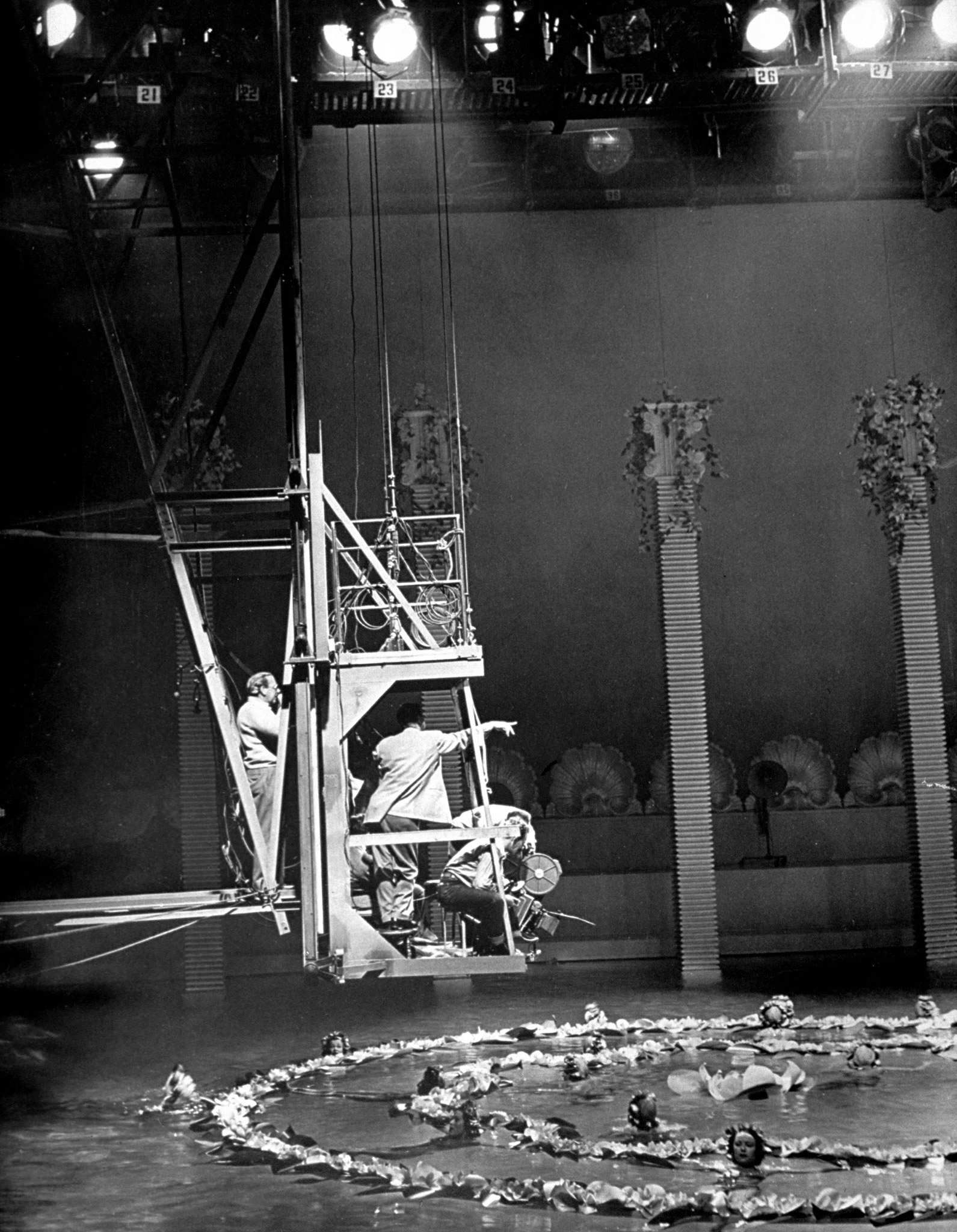 Movie director George Sidney riding on camera crane moving in closer while photographing a circle of swimmers amidst garlands of floating plastic flowers for a scene in the movie musical 'Bathing Beauty' starring Esther Williams in pool at M-G-M studios. 1944