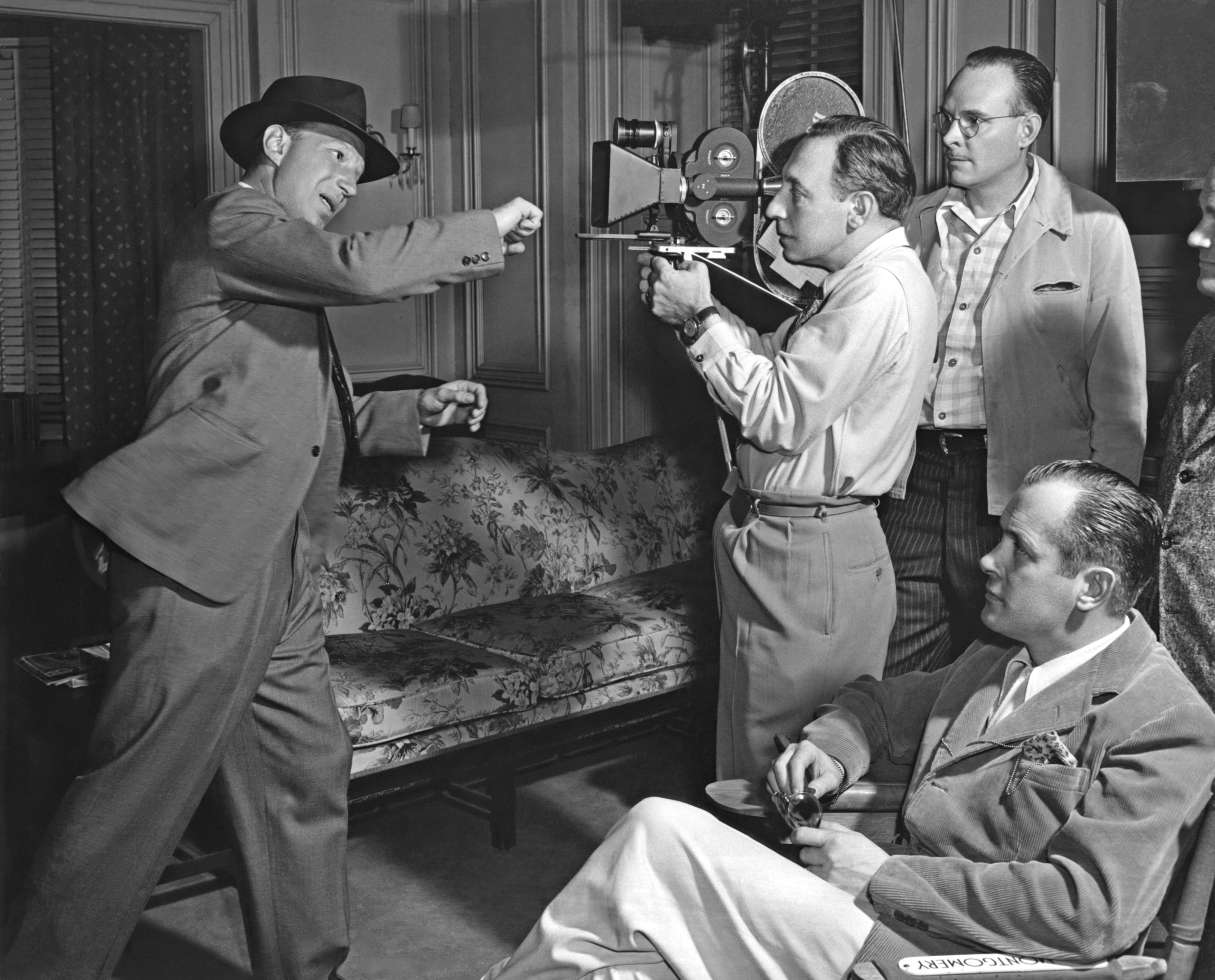 Lloyd Nolan throwing a punch towards cameraman Paul Vogel as actor-director Robert Montgomery looks on from his director's chair on the set of MGM's 'Lady in the Lake' in 1947.