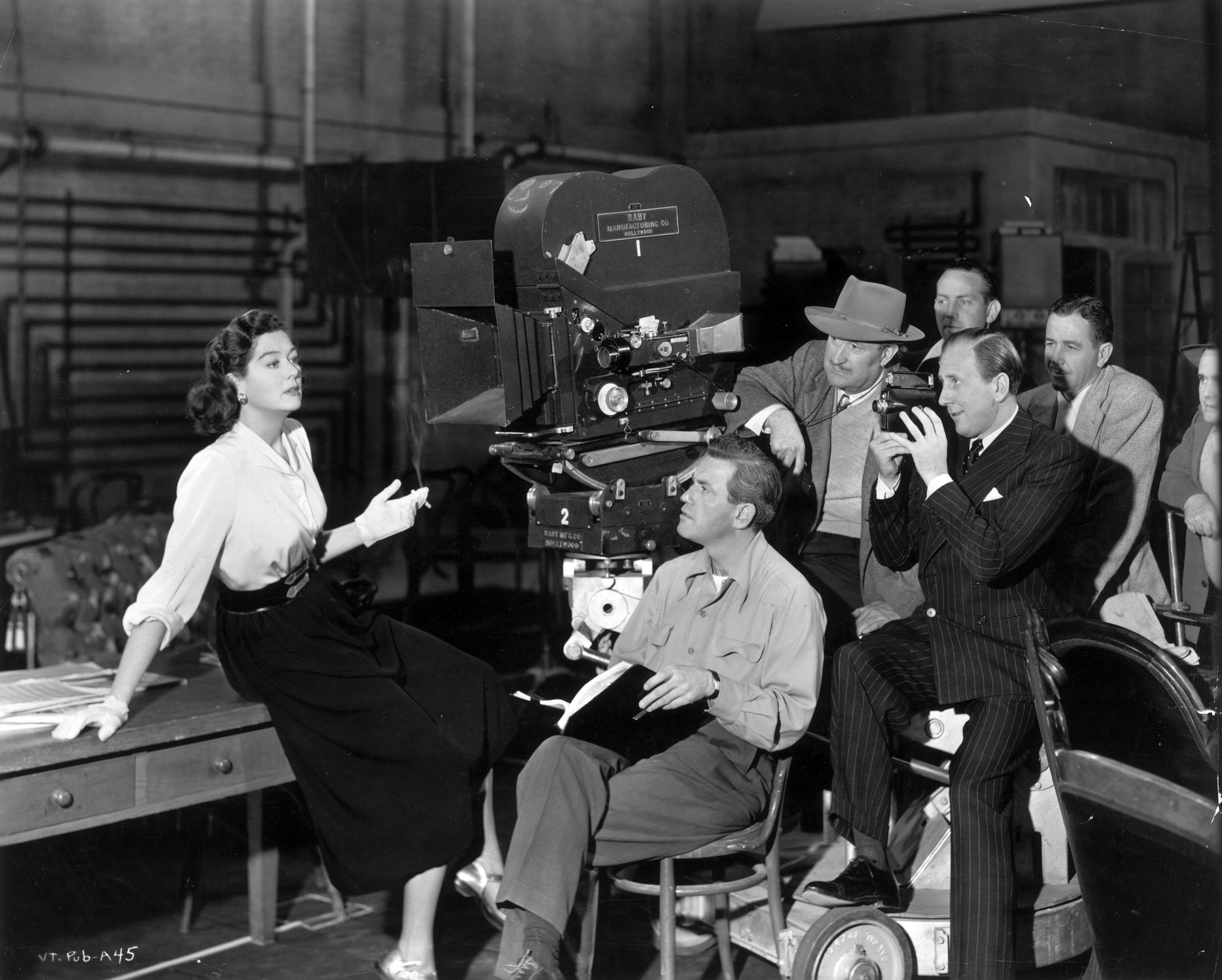 Rosalind Russell sits with her legs crossed on the edge of a wooden desk, holding a cigarette, as director John Gage and his crew film a scene on the set of 'The Velvet Touch'. 1948.