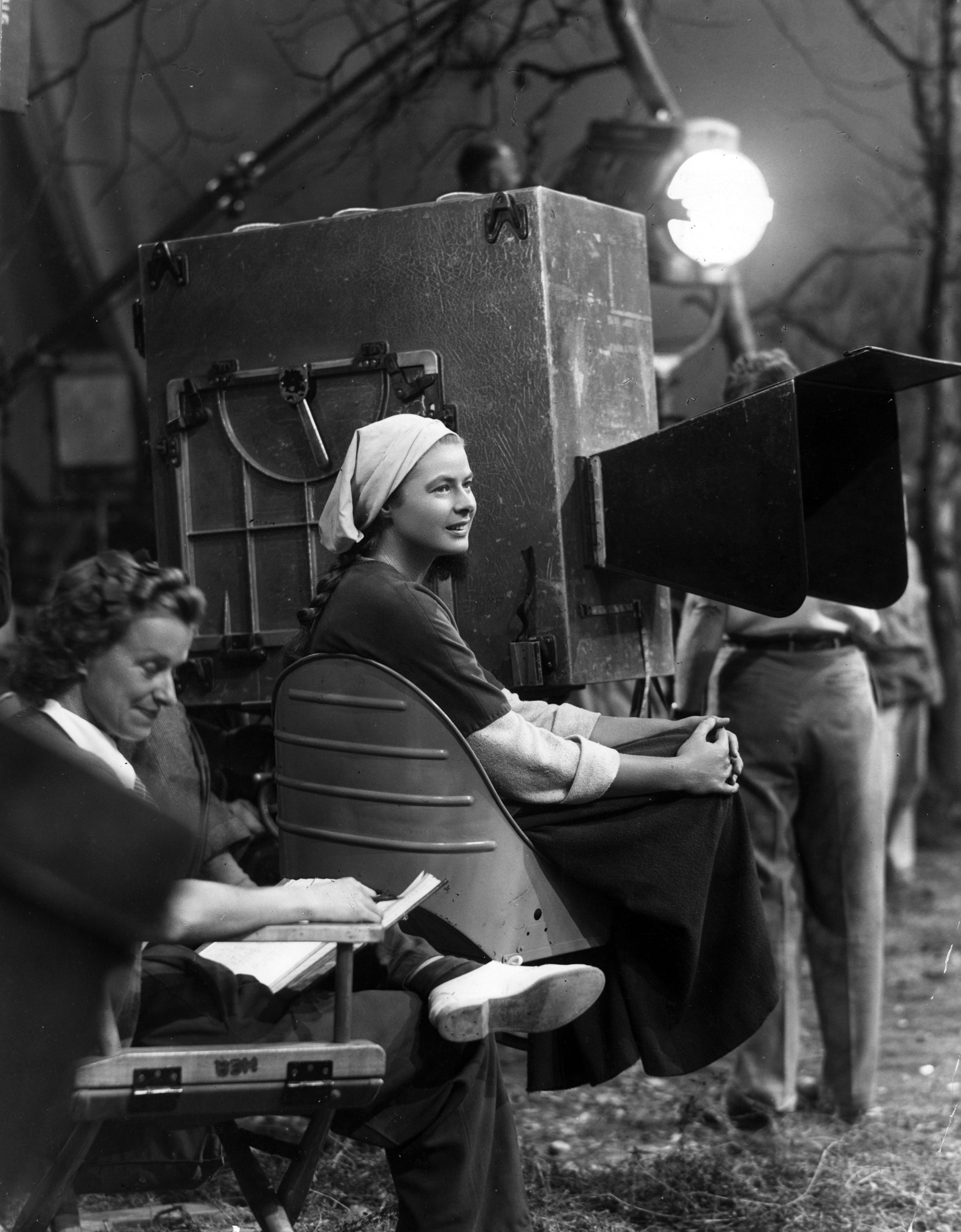 Ingrid Bergman sits next to the motion picture camera during a break in filming on the set of director Victor Fleming's film, 'Joan of Arc.' 1948.