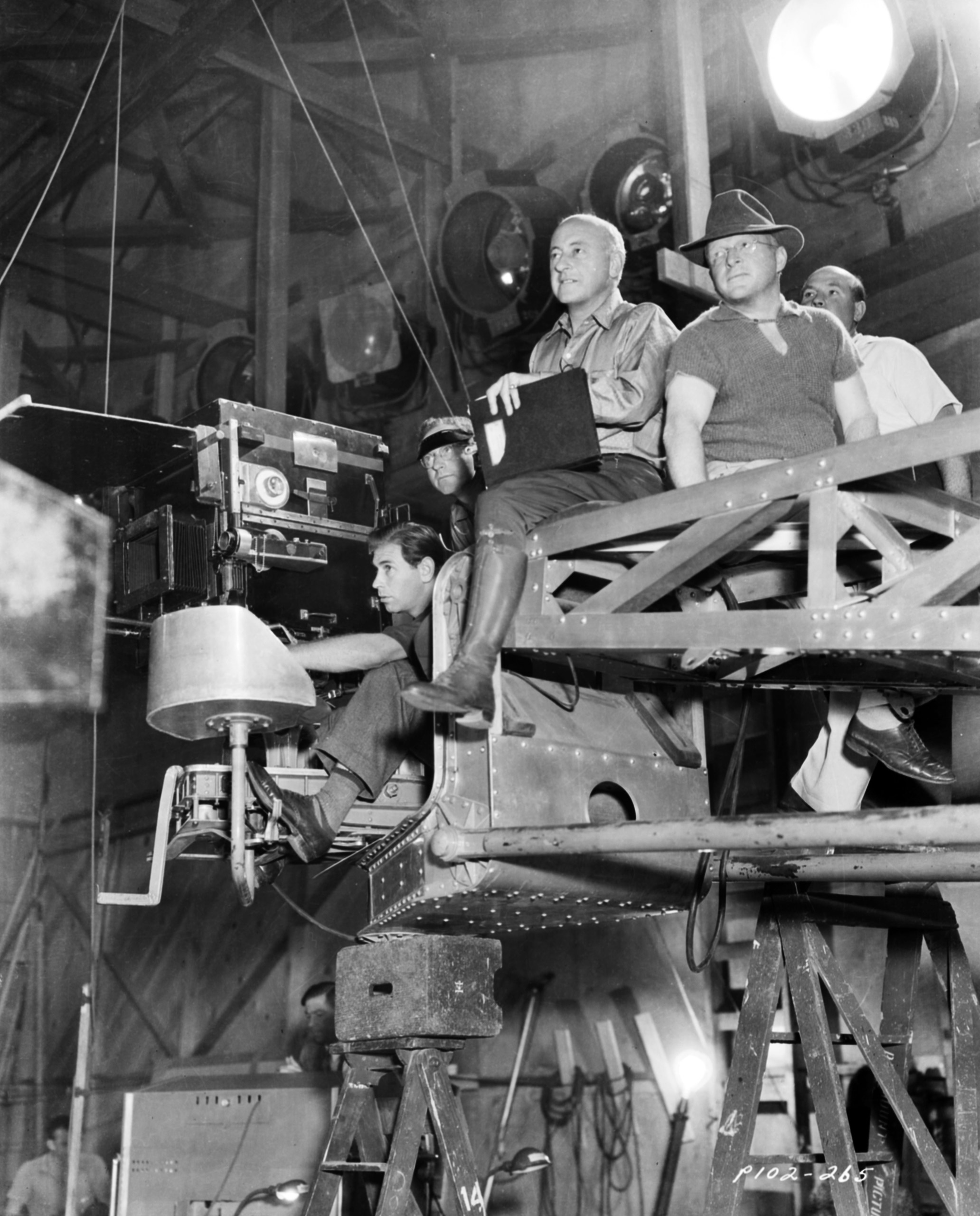 Cecil B DeMille sitting on a camera rig with members of his crew, on the set of the film 'Samson and Delilah', for Paramount Pictures, 1949.