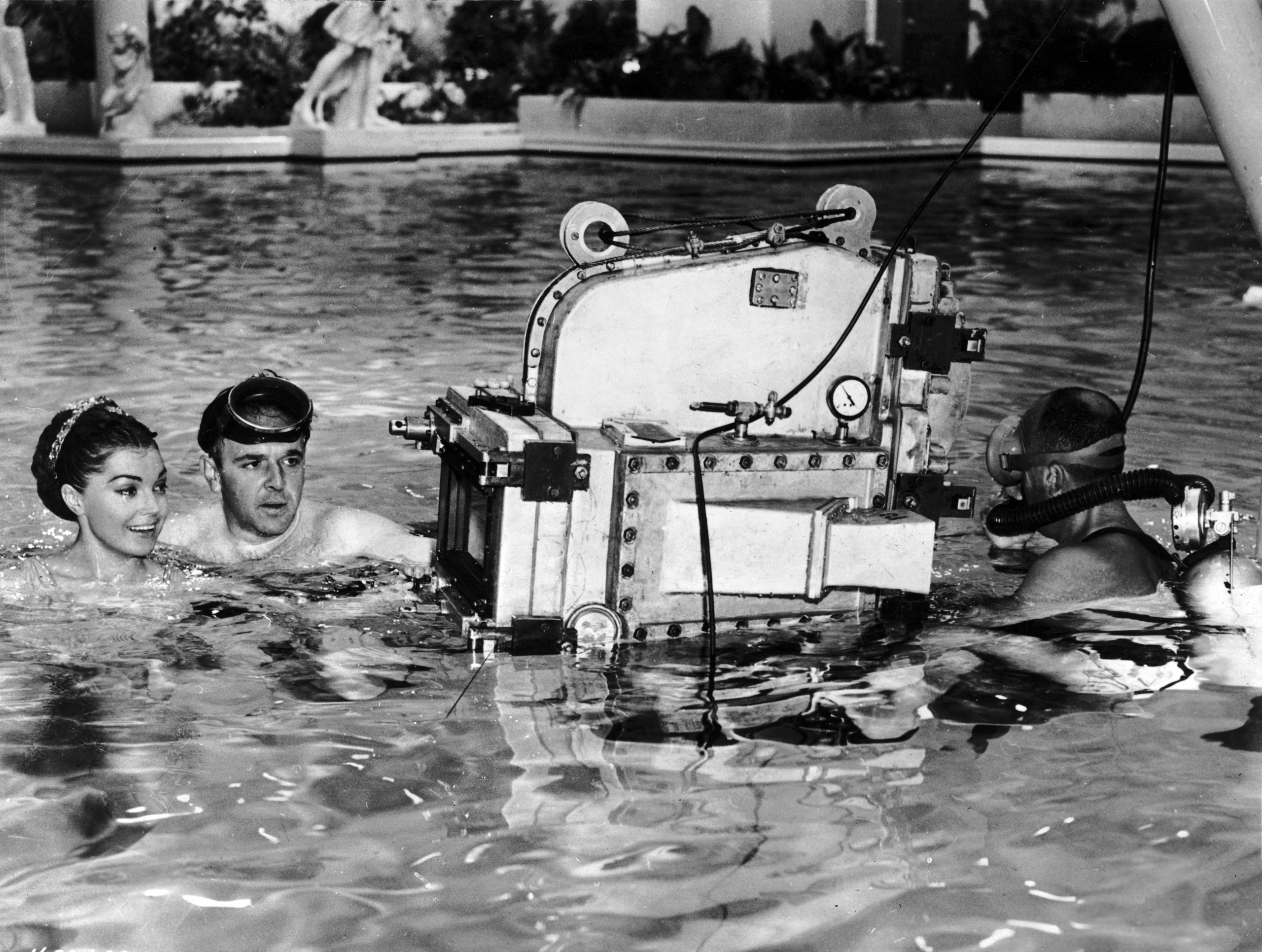 George Sidney wears a diving mask while directing American swimmer and actor Esther Williams in a swimming pool on the set of his film, 'Jupiter's Darling'. The camera man is wearing scuba apparatus. 1955.