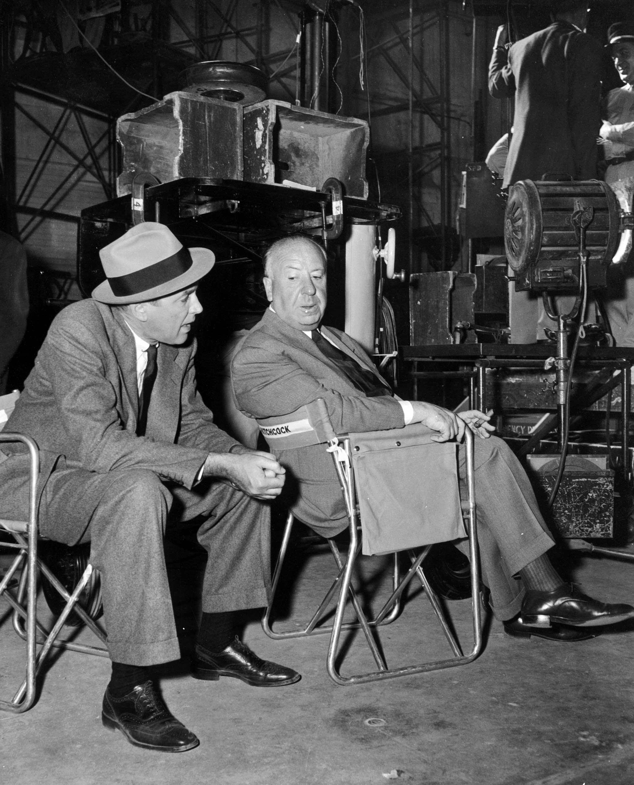 Alfred Hitchcock sitting with James Stewart on the set of his latest thriller 'The Man Who Knew Too Much'. 1956.