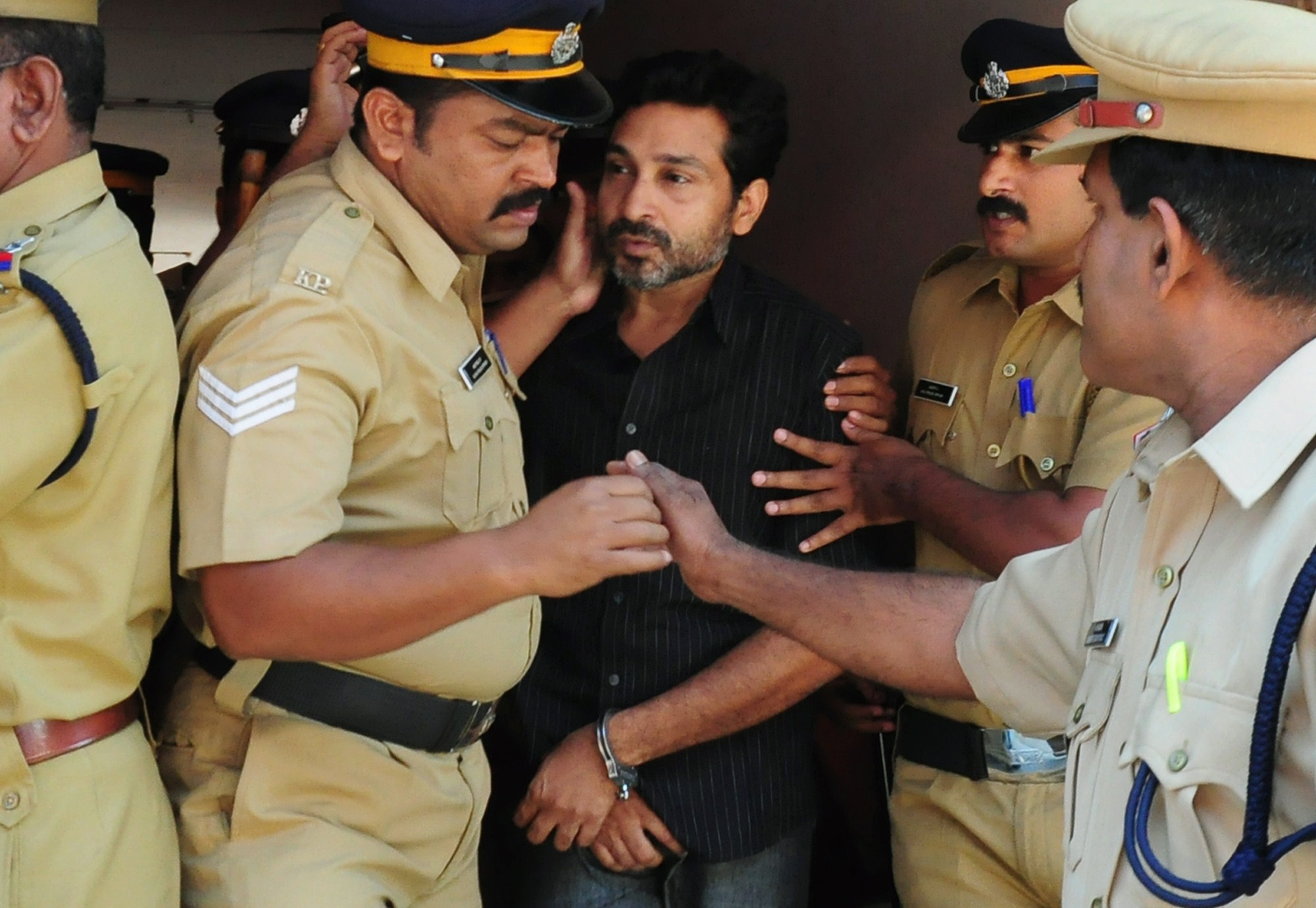 Indian police personnel escort Mohammed Nisham at the Judicial Magistrate's Court in Thrissur, India, on March 11, 2015. Nisham was sentenced to life in prison on Jan. 21, 2016