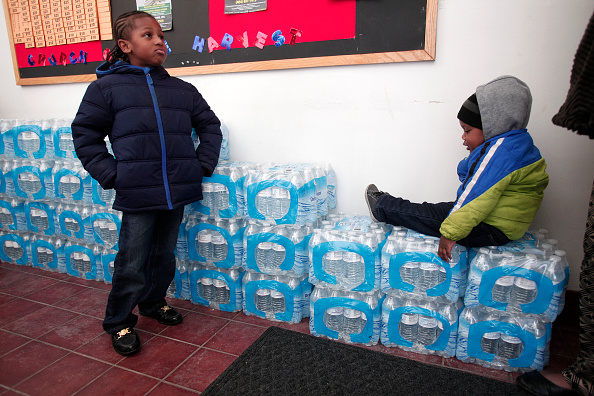 FLINT, MI - JANUARY 17:  Justin Roberson (L), age 6, of Flint, Michigan and Mychal Adams, age 1, of Flint wait on a stack of bottled water at a rally where the Rev. Jesse Jackson was speaking about about the water crises at the Heavenly Host Baptist Church January 17, 2016 in Flint, Michigan. U.S. President Barack Obama declared a federal emergency in Michigan, which will free up federal aid to help the city of Flint with lead contaminated drinking water. Michigan Gov. Rick Snyder requested emergency and disaster declarations after activating the National Guard to help the American Red Cross distribute water to residents.  Bill Pugliano—Getty Images