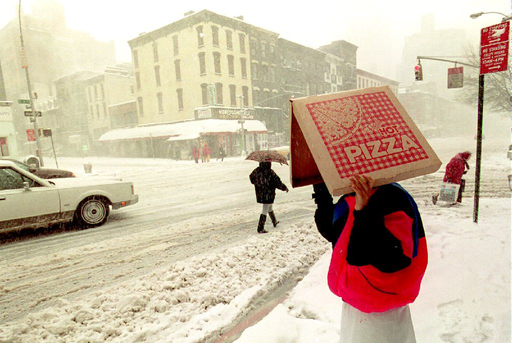 A pizza delivery man shields himself from the blizzard conditions pounding New York City and most of the east coast of the U.S. as he waits to cross Second Avenue.