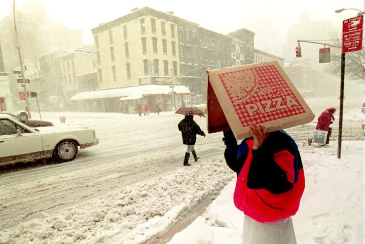 A pizza delivery man shields himself from the bliz
