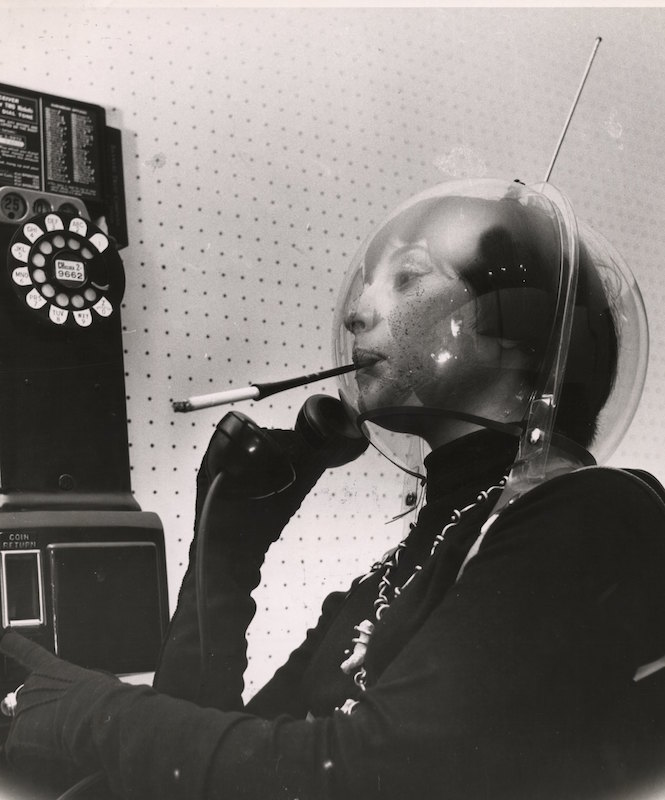 A young woman wears a plastic globe on her head, like an alien or an astronaut, smoking a cigarette in a holder and holding the receiver of a pay telephone, in Greenwich Village, New York, New York, mid 1950s.