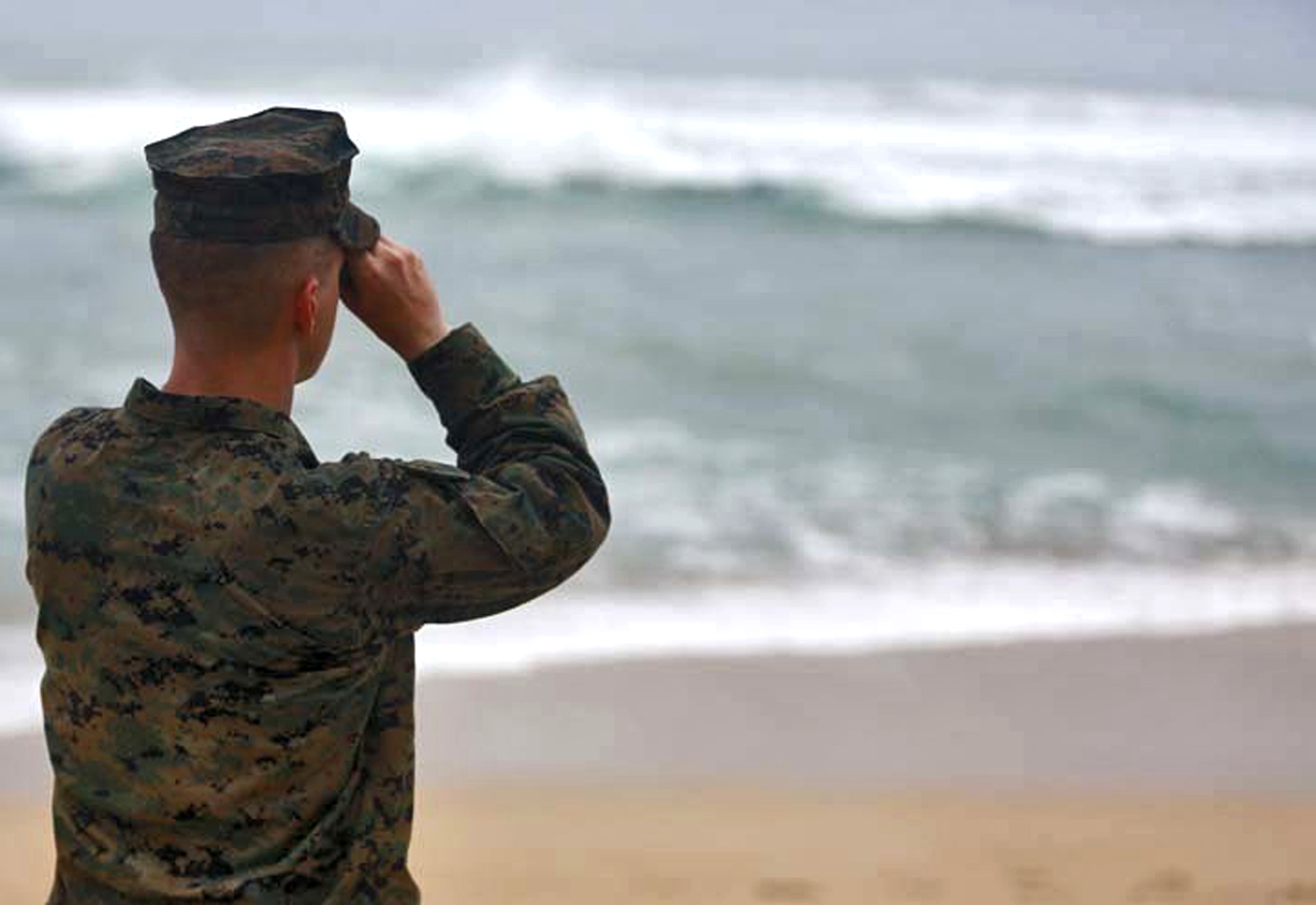 This photo provided by the U.S. Marine Corps shows an officer searching for debris of a helicopter mishap in Haliewa Beach Park, Hawaii on Jan. 15, 2016.