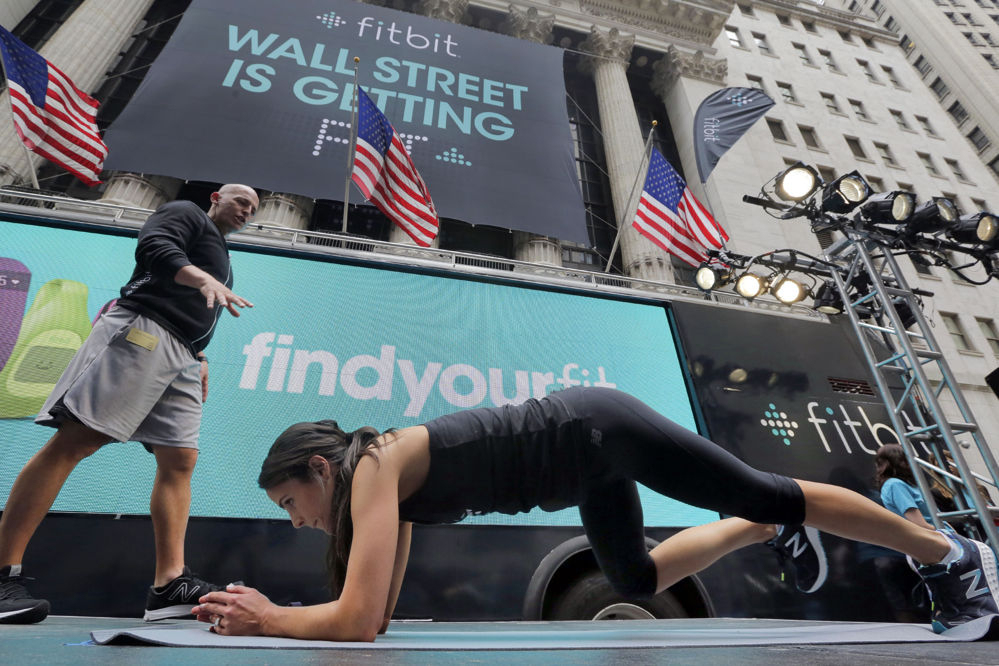 From left: Fitness expert Harley Pasternak and actress Jordana Brewster lead a work out on behalf of Fitbit, in front of the New York Stock Exchange, June 18, 2015.