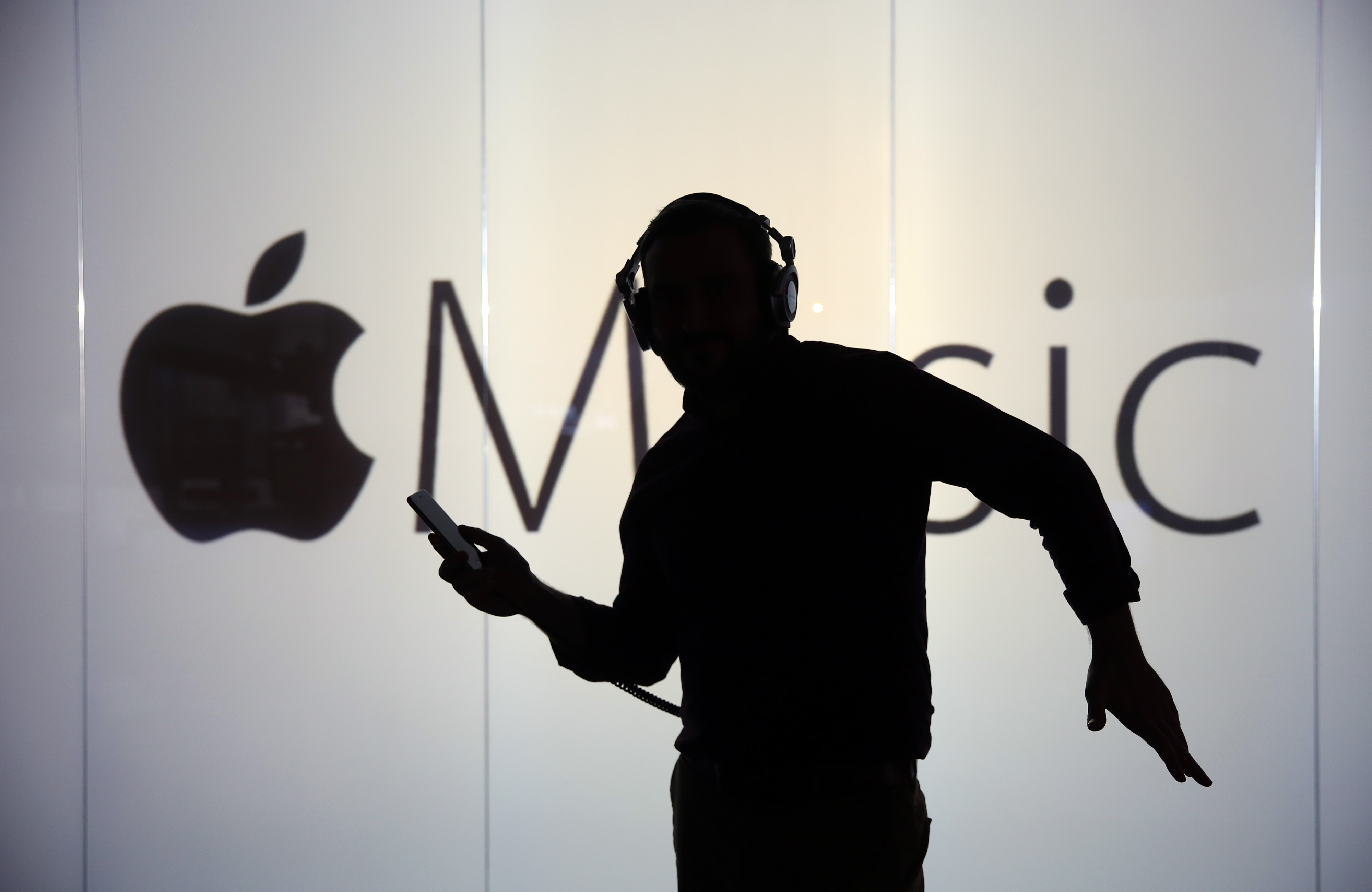 A man dances to music being streamed on his Apple Inc. iPhone 6s whilst framed against a wall bearing the Apple music symbol in this arranged photograph in London on Dec. 23, 2015.