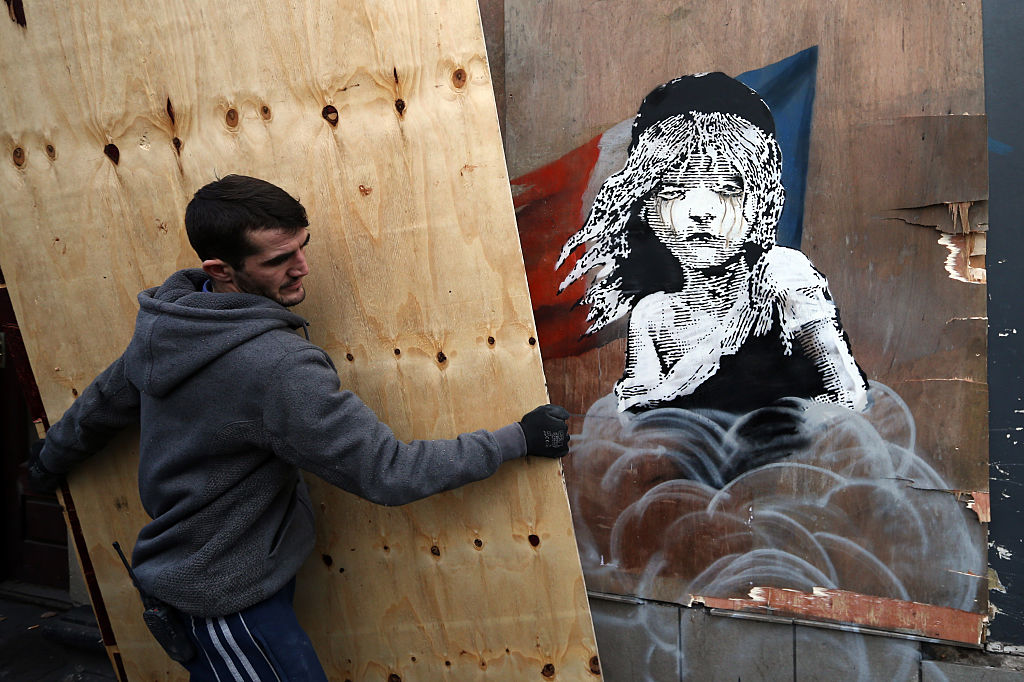 "The artwork features a girl from the musical ""Les Miserables"" with tears in her eyes as a can of teargas billows up from the ground."