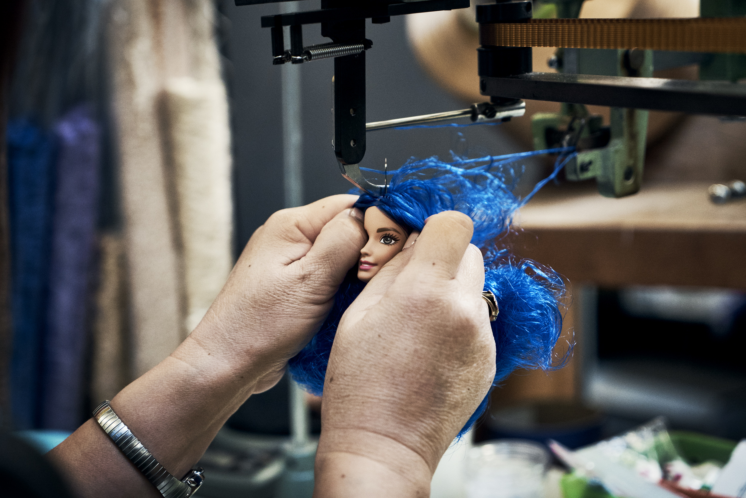 "A special machine attaches curvy Barbie's  hair. The process is called ""rooting."""