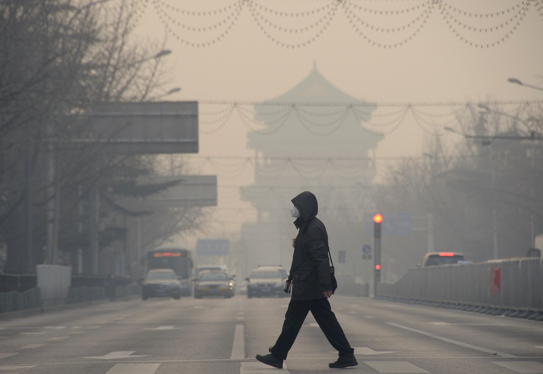 A pedestrian walks amid heavy smog in Beijing on Dec. 29, 2015.