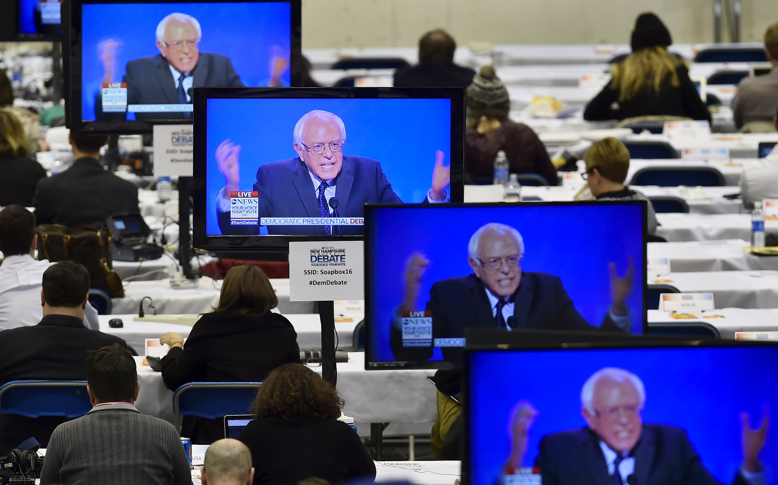 Bernie Sanders appears on television screens in the media work-room during the Democratic presidential candidates debate at Saint Anselm College in Manchester, N.H., on Dec. 19, 2015.