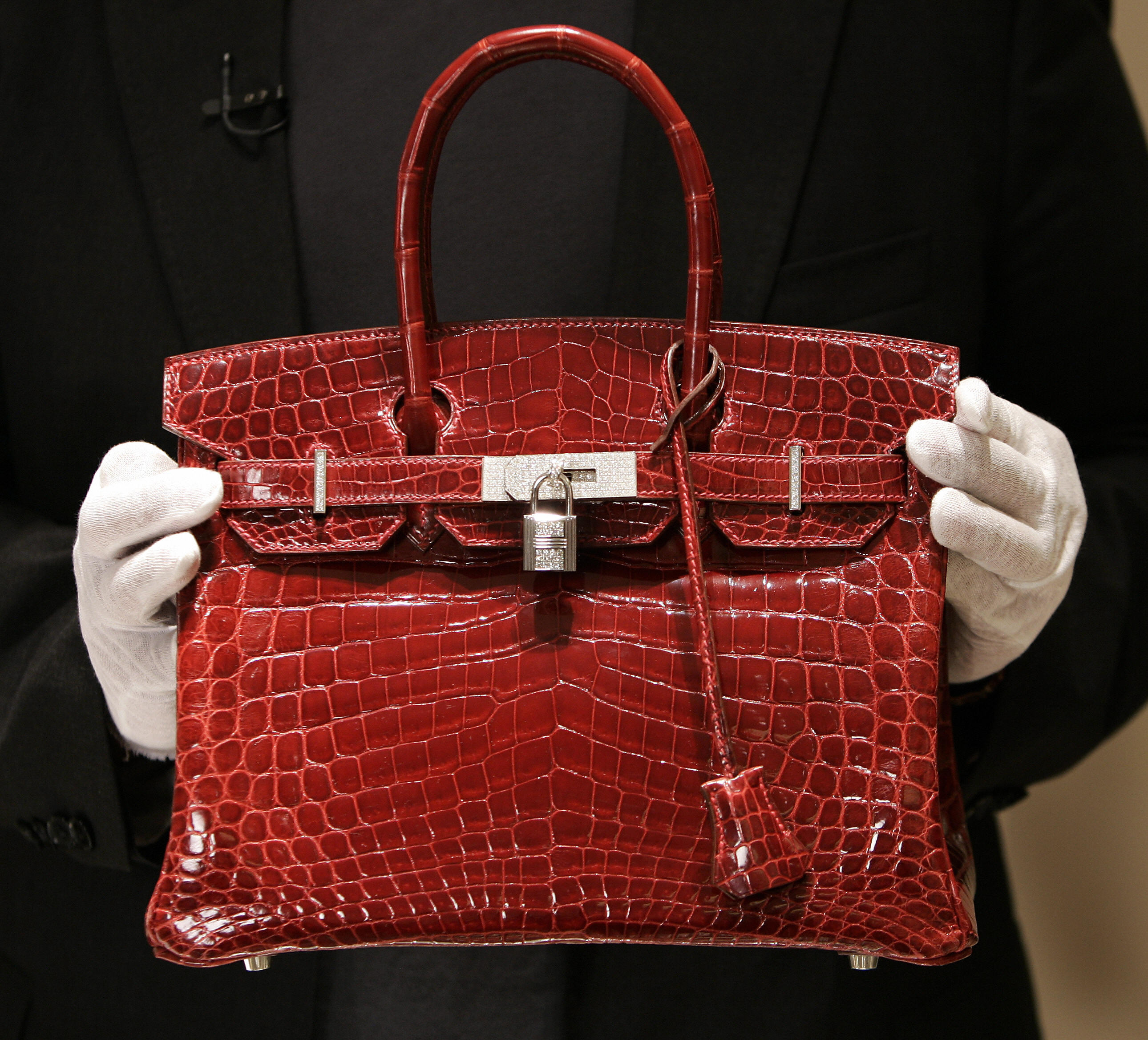A employee holds a $129,000 crocodile Hermes Birkin Bag during a private opening for the new Hermes store on Wall Street in New York 21 June 2007.
