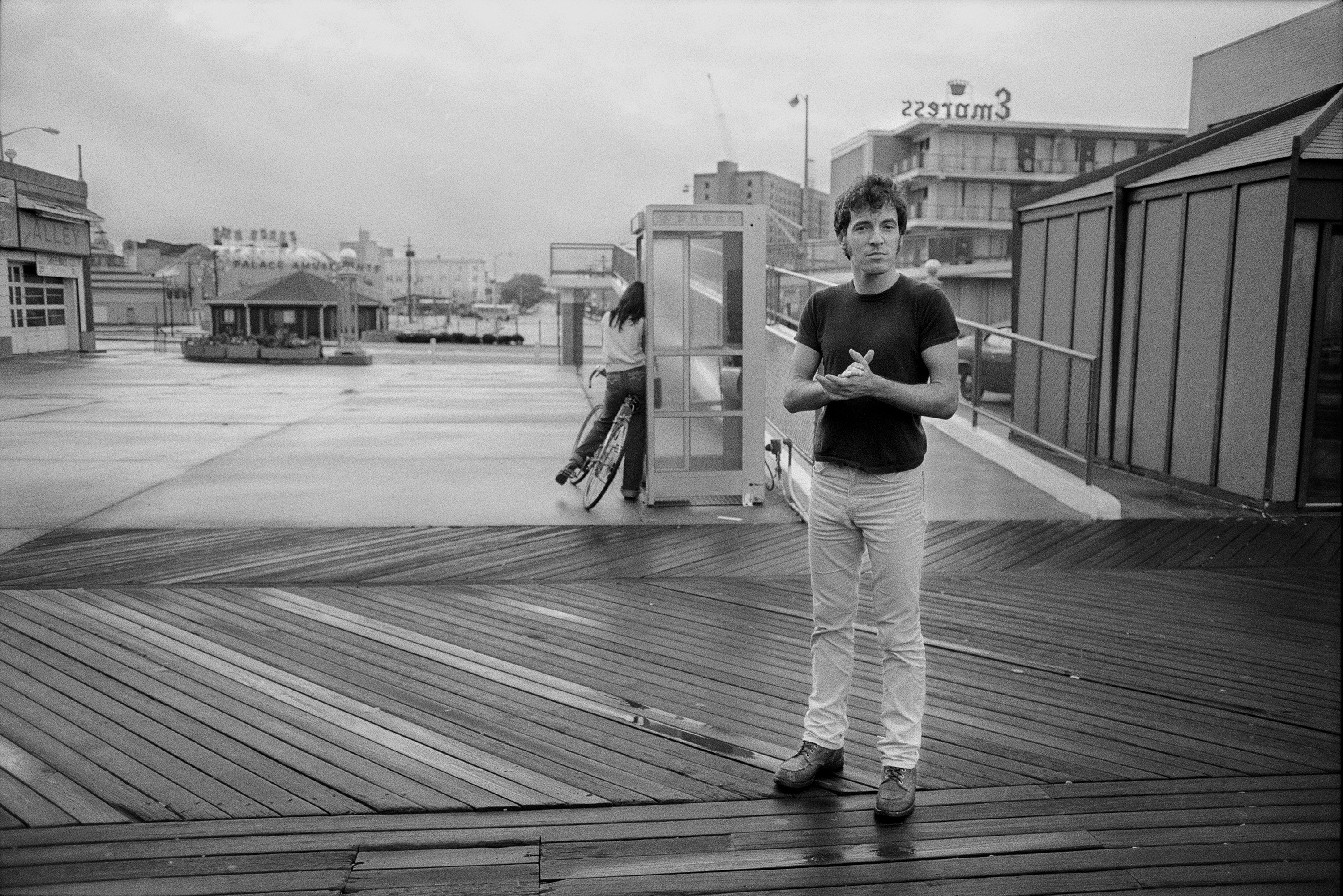 """Bruce Springsteen on the boardwalk by the Empress Hotel in Asbury Park, N.J.,  Aug. 1979. This photograph was chosen as the cover image for the """"Hungry Heart"""" single."""