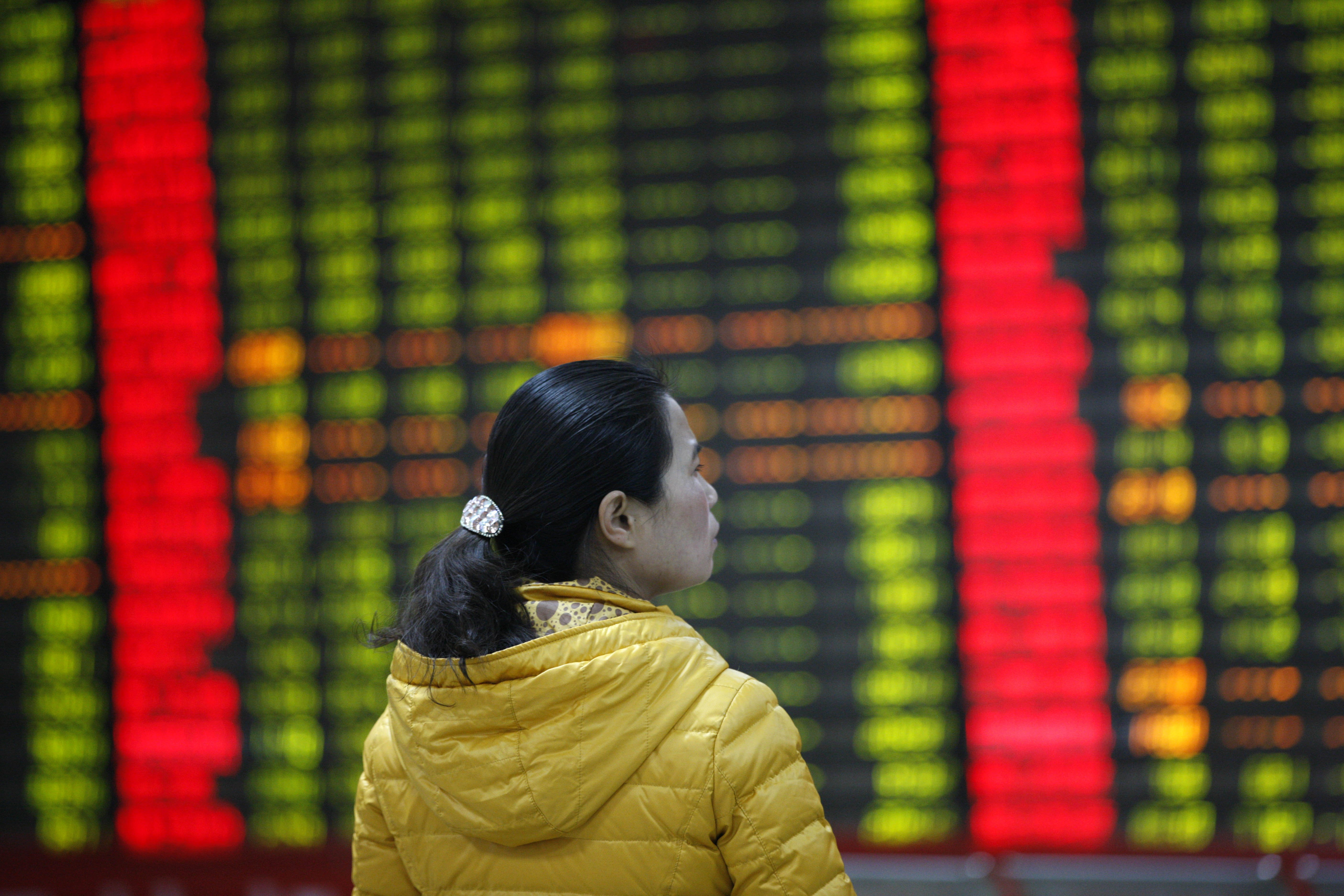 An investor watches electric boards in a stock market in Huaibei, Anhui province, east China on Jan. 7, 2016.