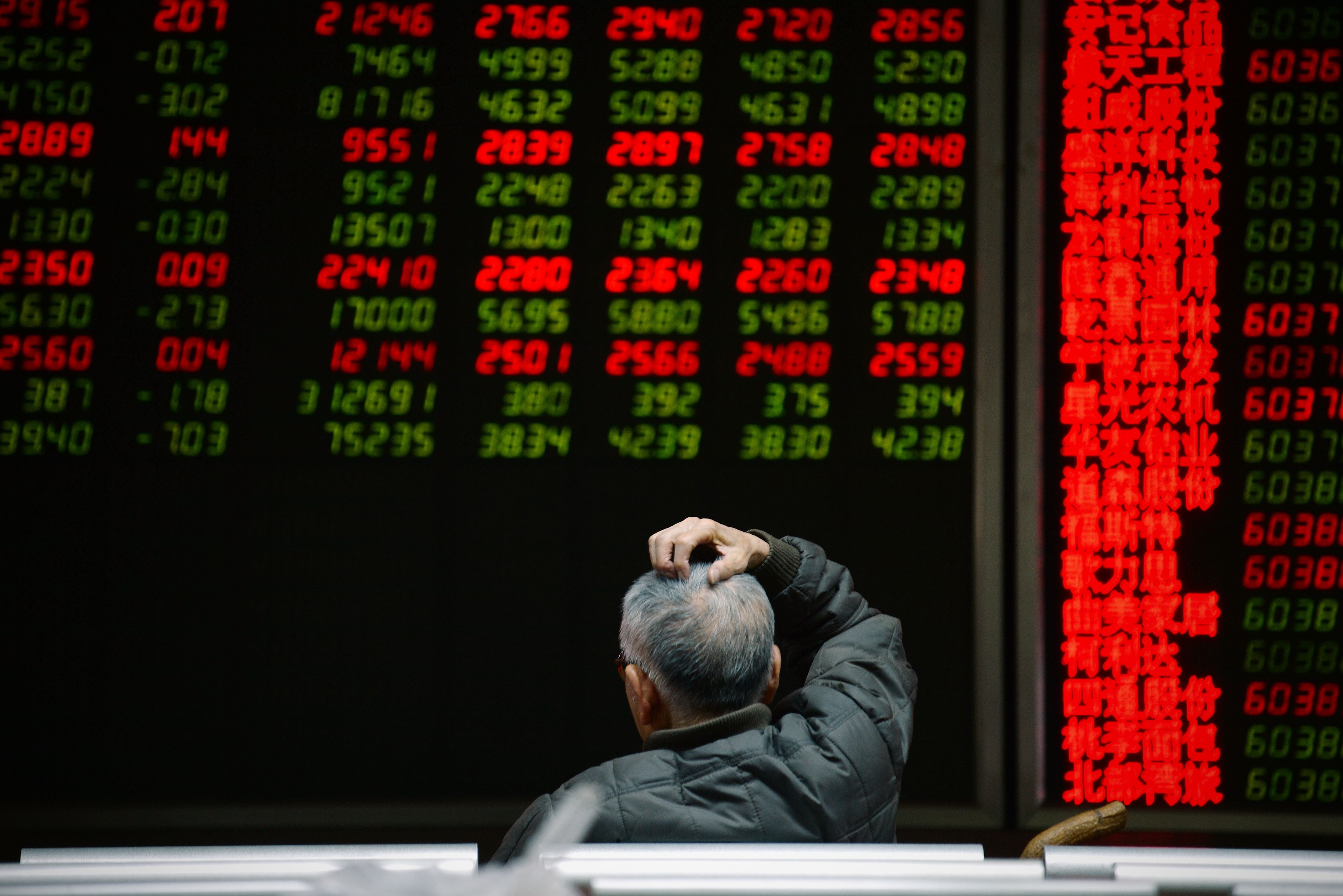 An investor looks at screens showing stock market movements at a securities company in Beijing on Jan. 14, 2016.