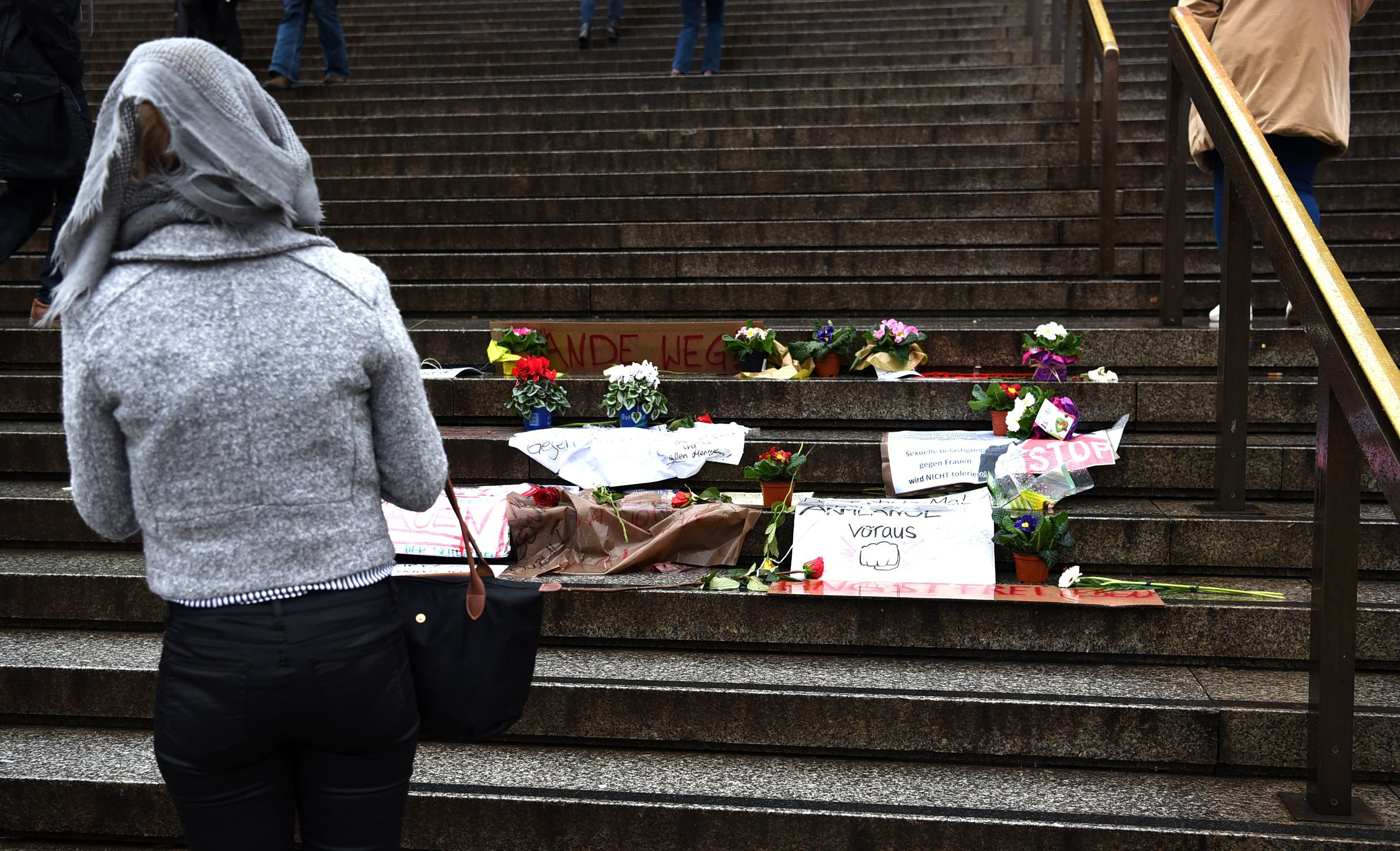 A woman looks at flowers and letters of protest that are laid down on the steps in front of the Cologne main train station in Cologne, western Germany on Jan. 11, 2016.