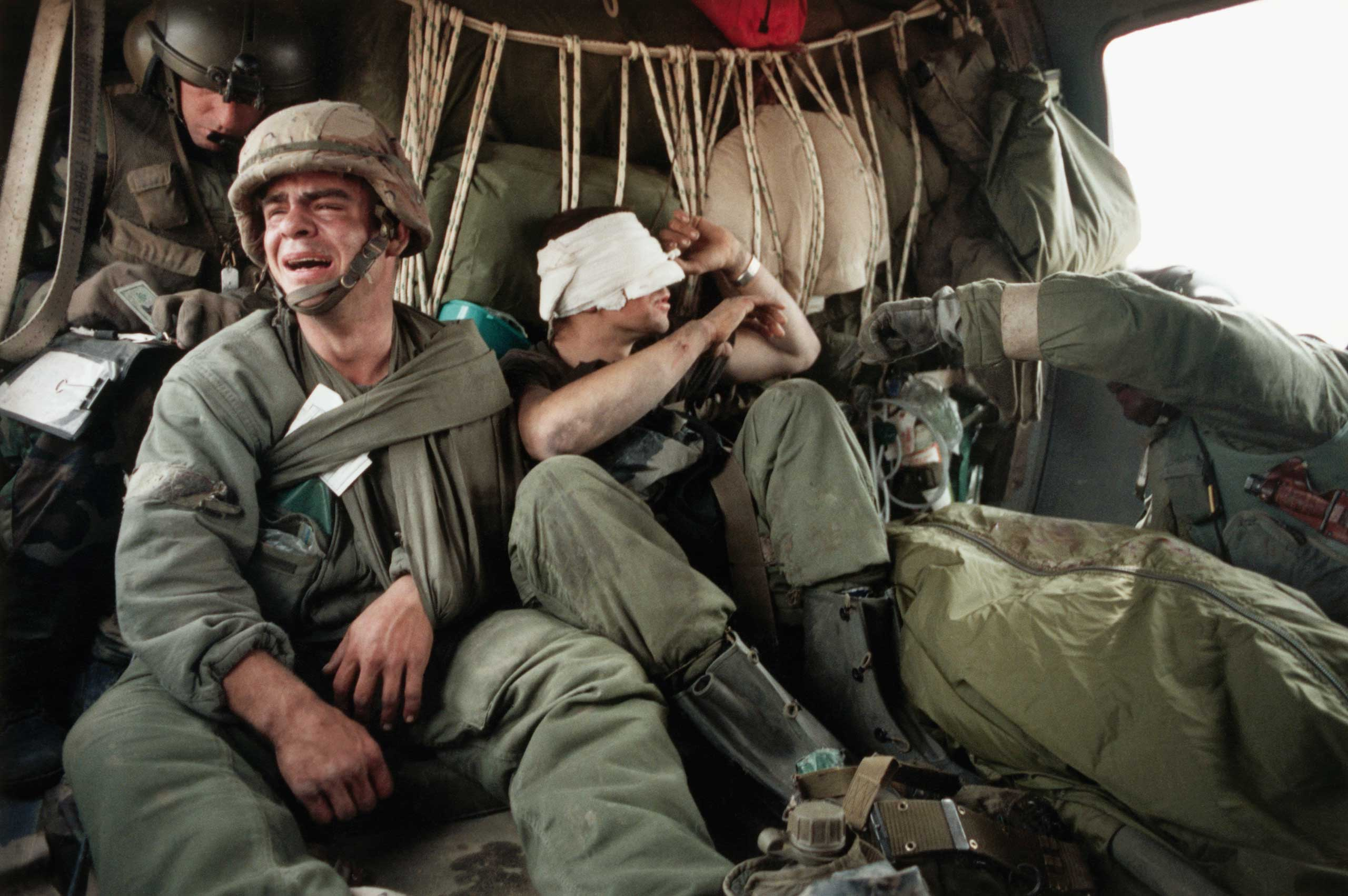 Ken Kozakiewicz (left) breaks down in an evacuation helicopter after hearing that his friend, the driver of his Bradley Fighting Vehicle, was killed in a  friendly fire  incident that he himself survived. All of the soldiers were exposed to depleted uranium as a result of the explosion. They and the body of the dead man are on their way to a MASH (Mobile Army Surgical Hospital). Iraq, 1991.