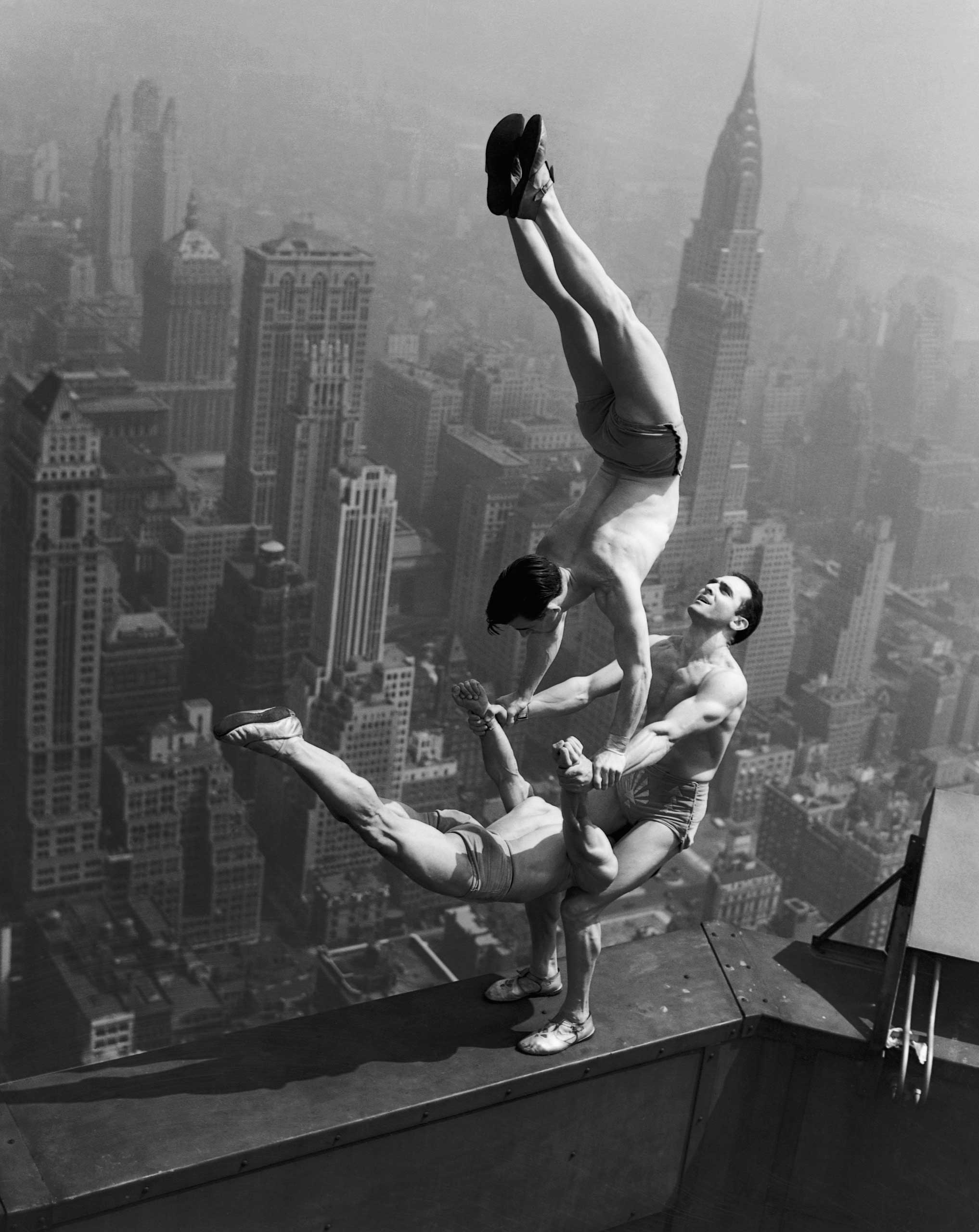 Acrobats Jarley Smith (top), Jewell Waddek (left), and Jimmy Kerrigan (right) perform a delicate balancing act on a ledge of the Empire State Building in Manhattan. Aug. 21, 1934,