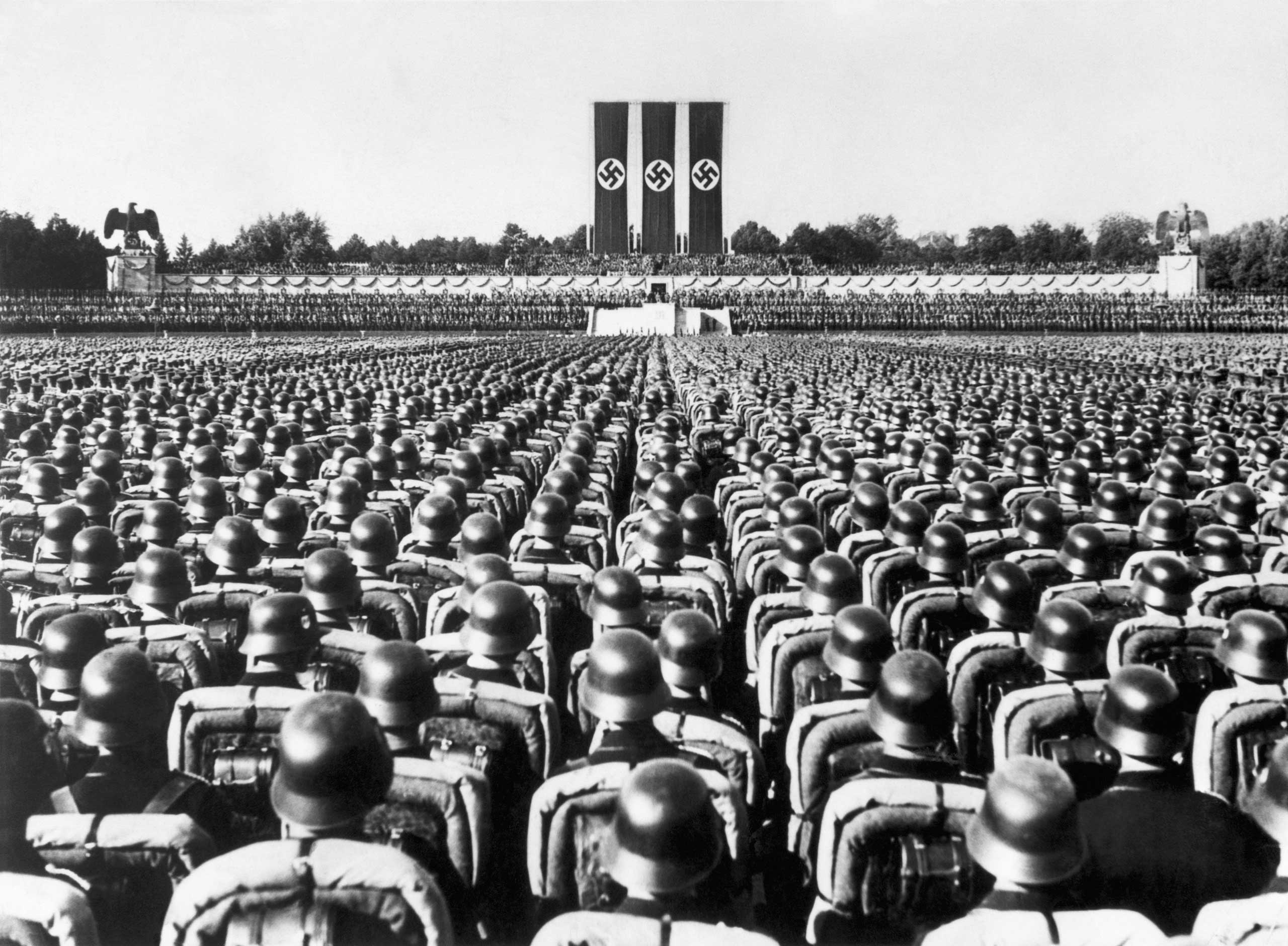 A huge crowd of soldiers in combat gear stands at attention beneath the reviewing stand at Nuremberg, Germany, listening to a speech by the German Fuhrer, Adolf Hitler during the Nazi Party rally of 1936.