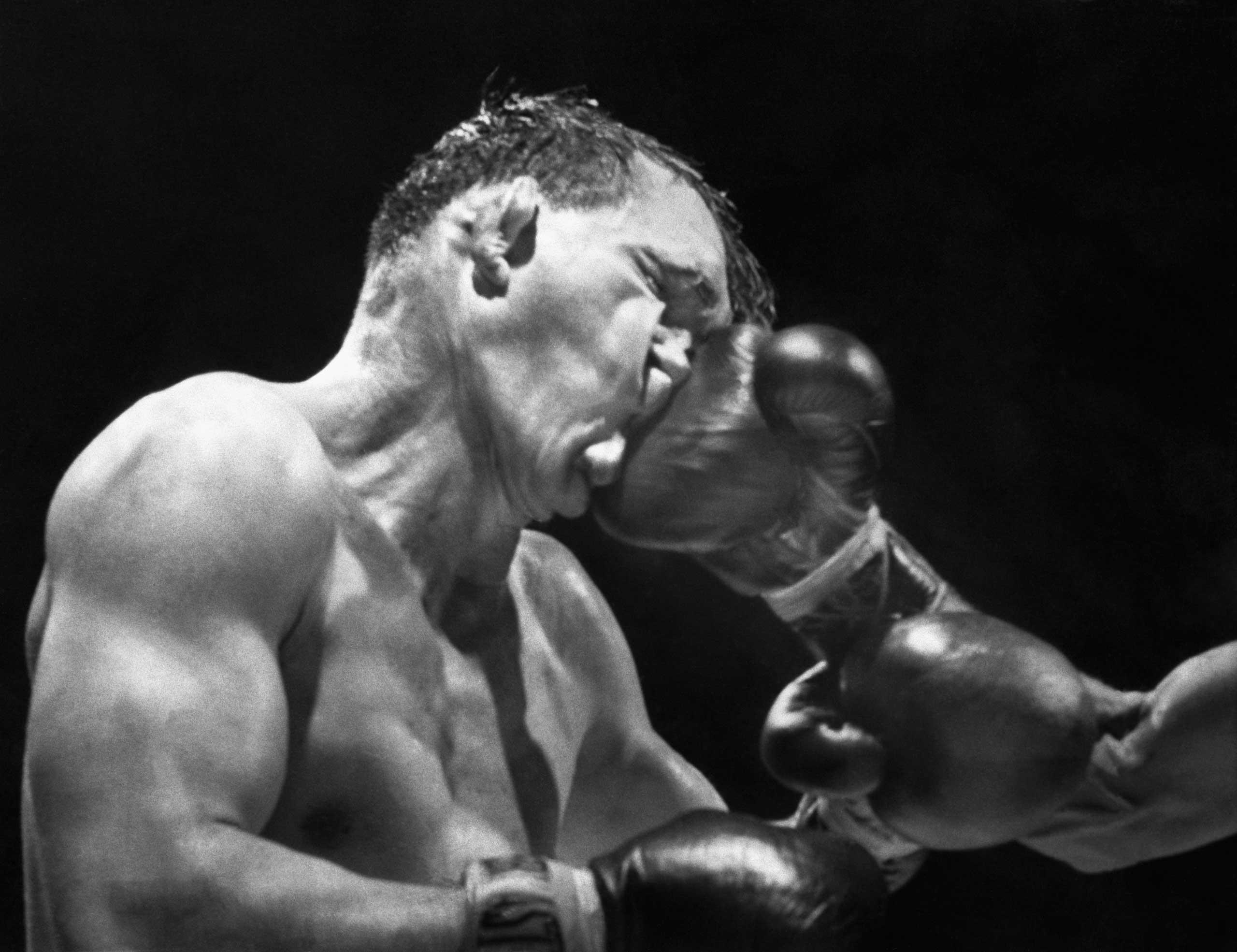 Gene Fullmer receives a crushing right from Neal Rivers during their 10-round bout at Madison Square Garden. Fullmer, a former middleweight champion, would go on to win the bout by a majority decision. Nov. 15, 1957.