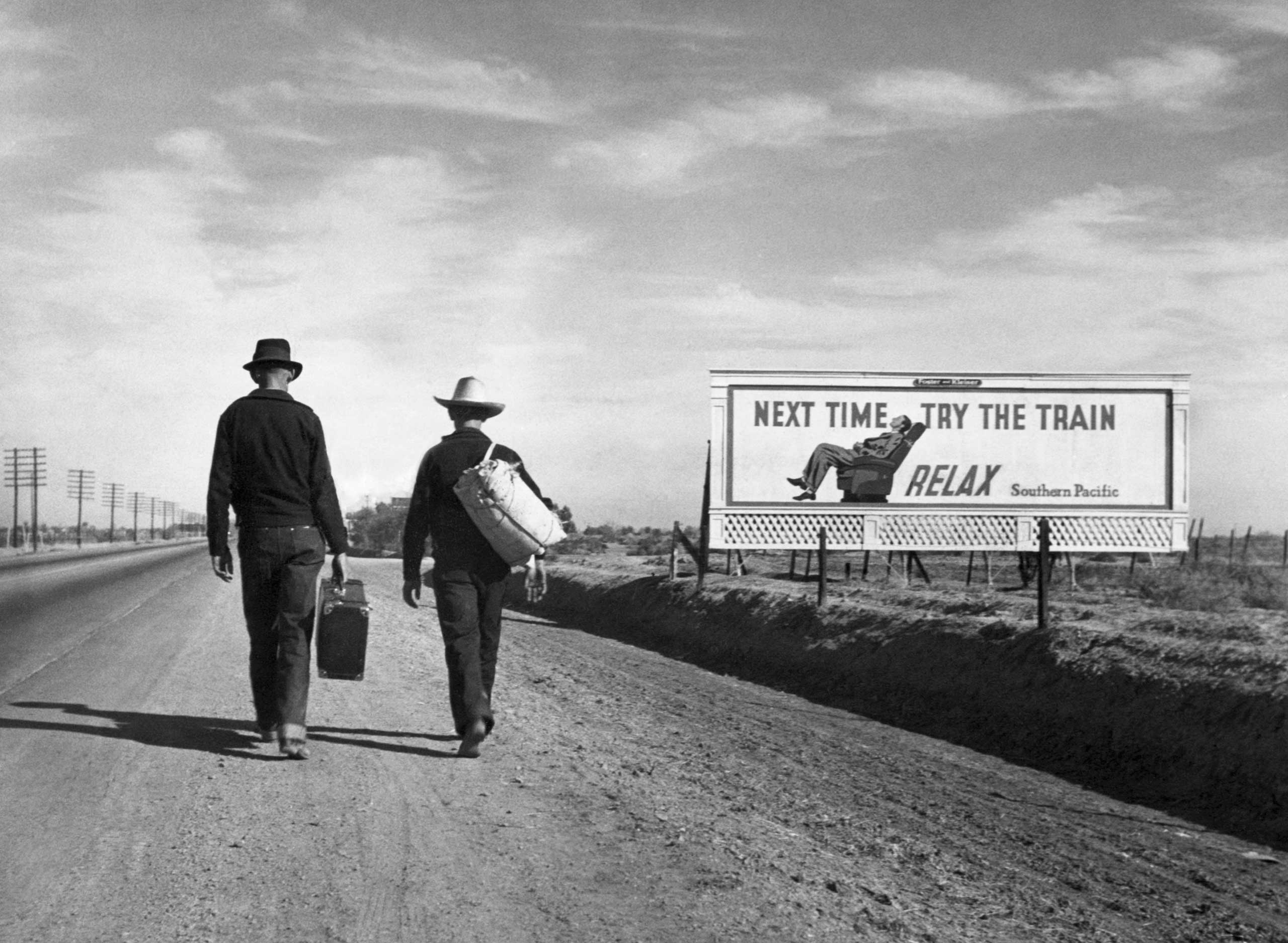 Two Dust Bowl refugees walk along a highway towards Los Angeles. passing by a billboard imploring them  Next Time Try the Train - Relax . March 1937.