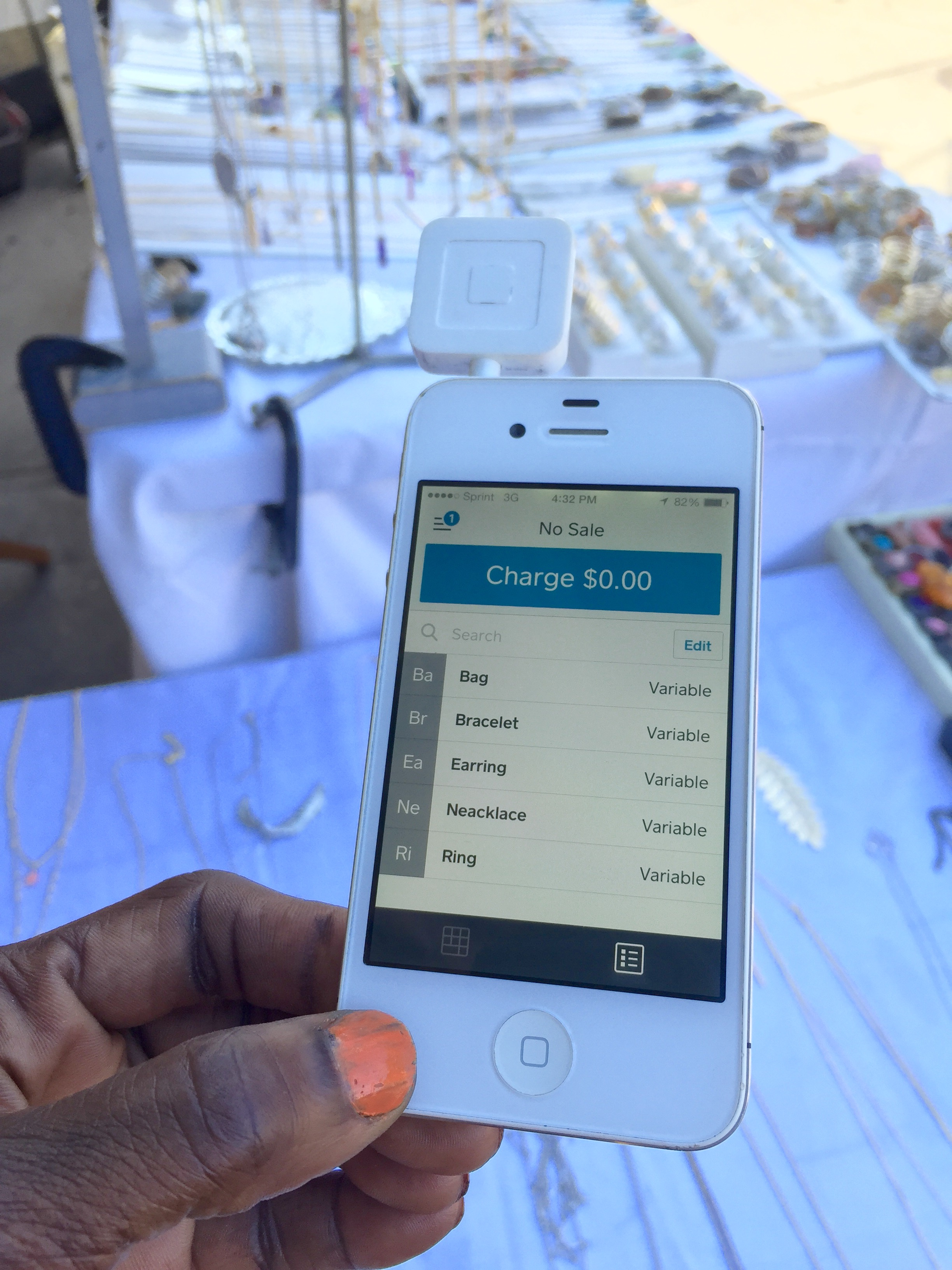 Technology Helps: A jewelry vendor at an outdoors craft market holds her credit card reader attached to a smart device for mobile point of sales activity