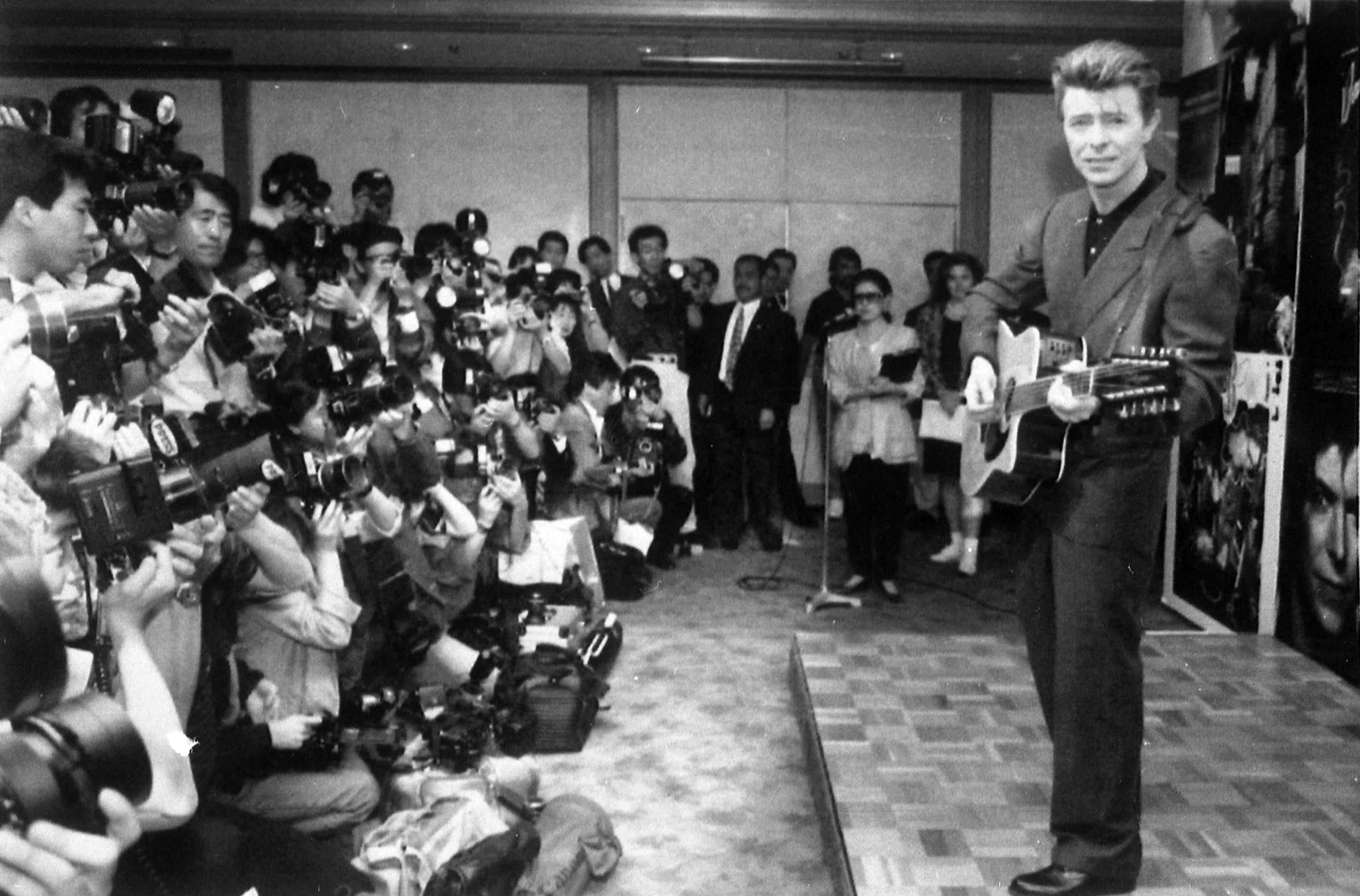 David Bowie plays an acoustic guitar while being photographed at a press conference in Tokyo on May 19, 1990.