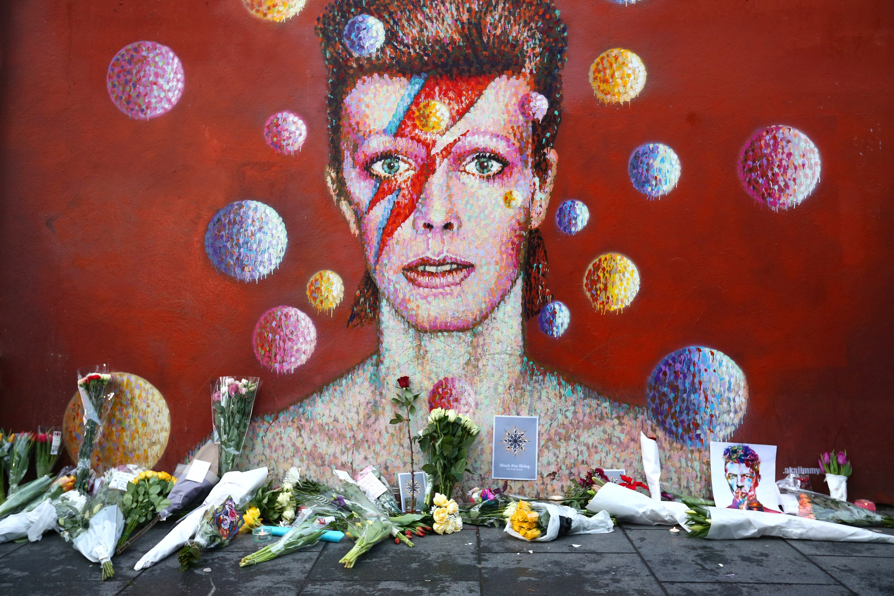 Flowers are laid beneath a mural of David Bowie in Brixton, England on Jan. 11, 2016. British music and fashion icon David Bowie died earlier today at the age of 69 after a battle with cancer.
