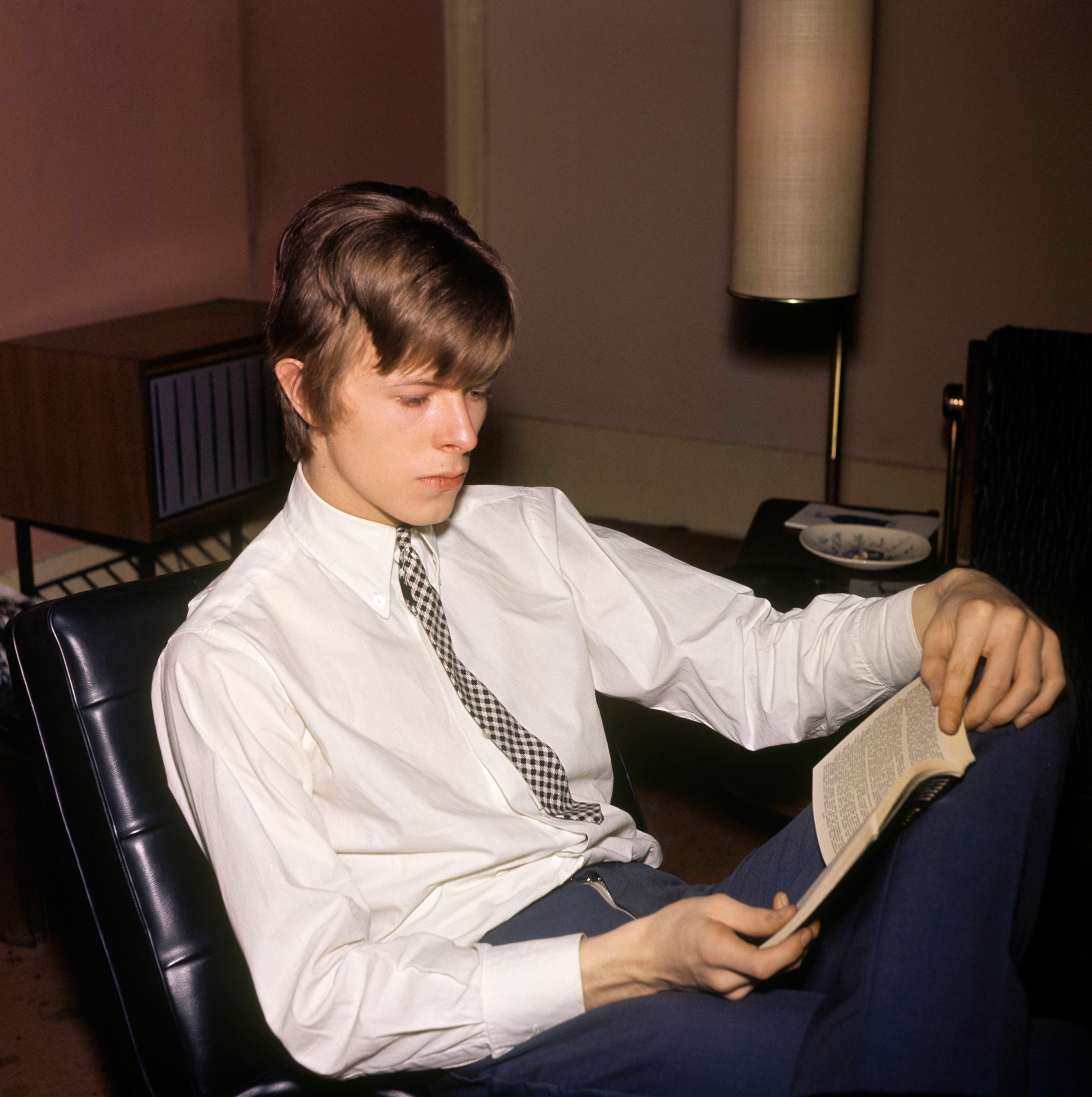 David Bowie photographed reading a book, c. 1965.
